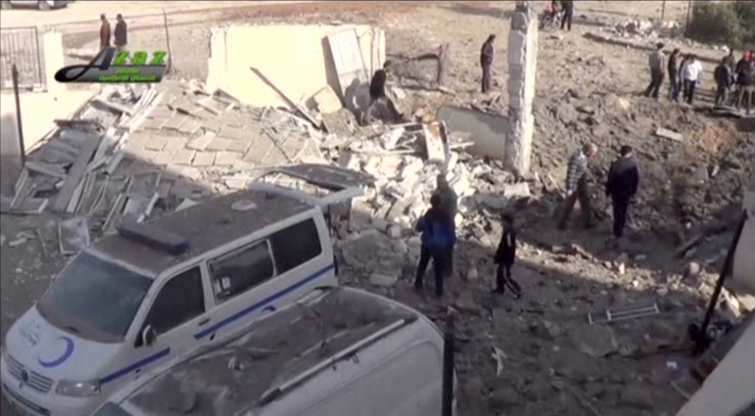 Syrian civilians stand in the rubble of a ruined building