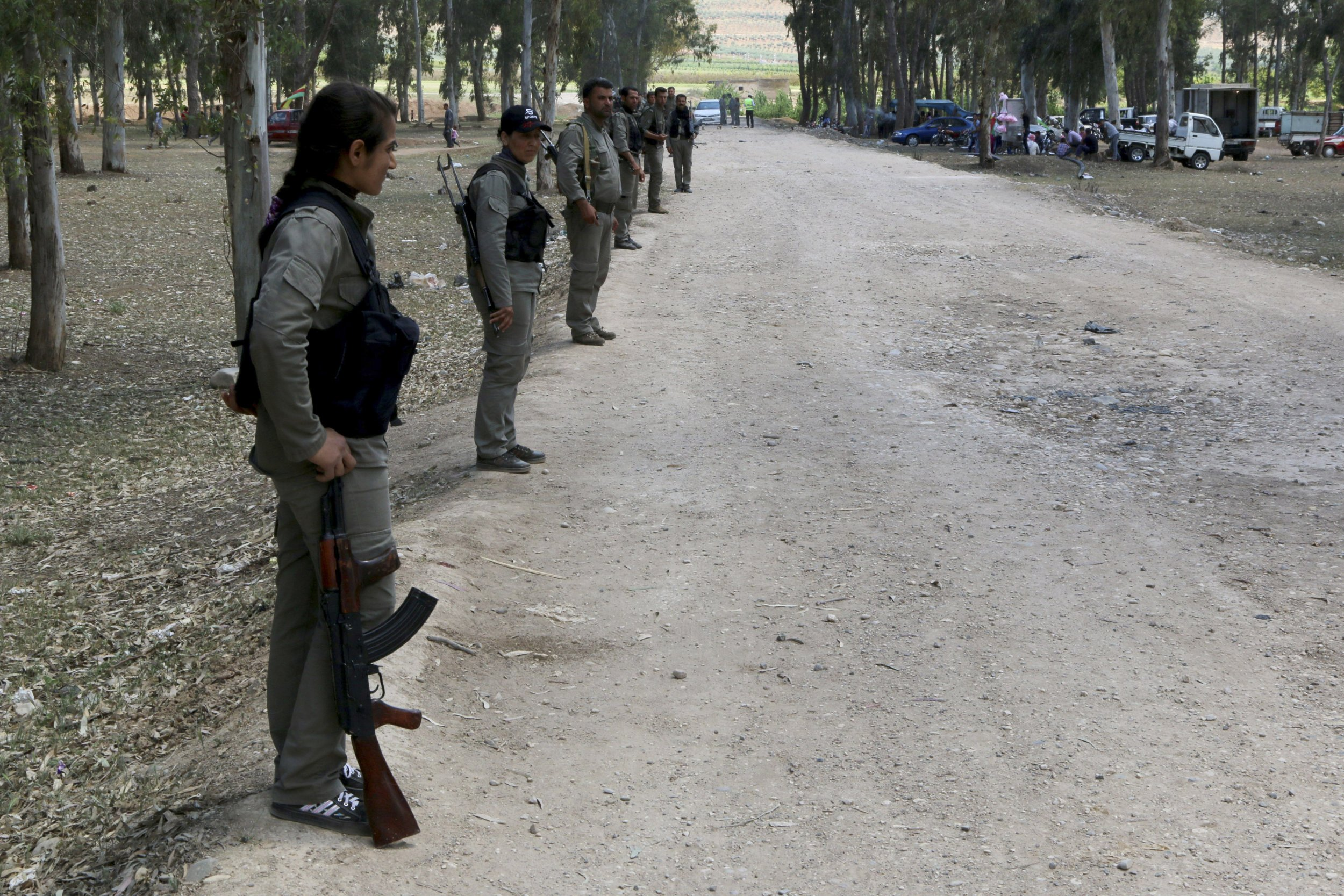 Kurdish fighters line the length of a road