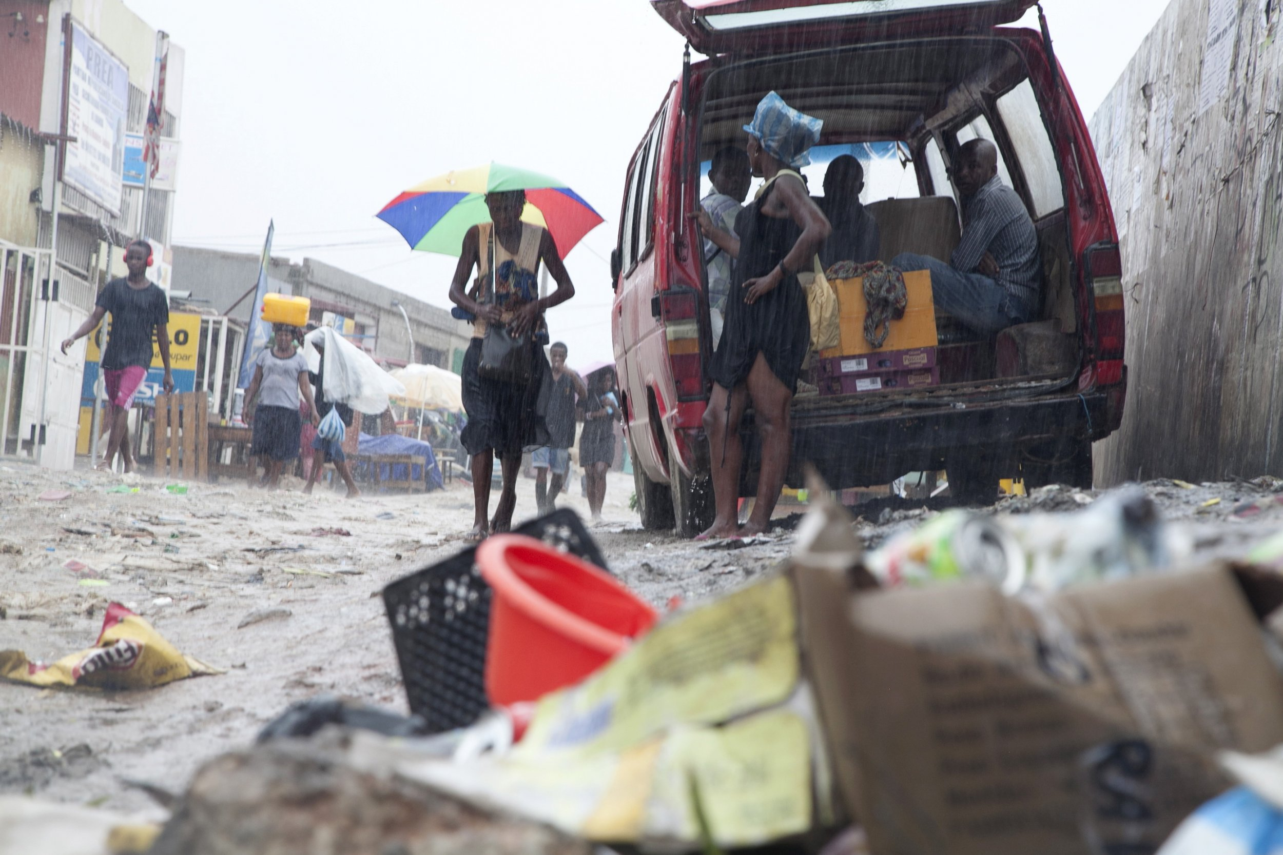 Angola residents walk through a pile of garbage
