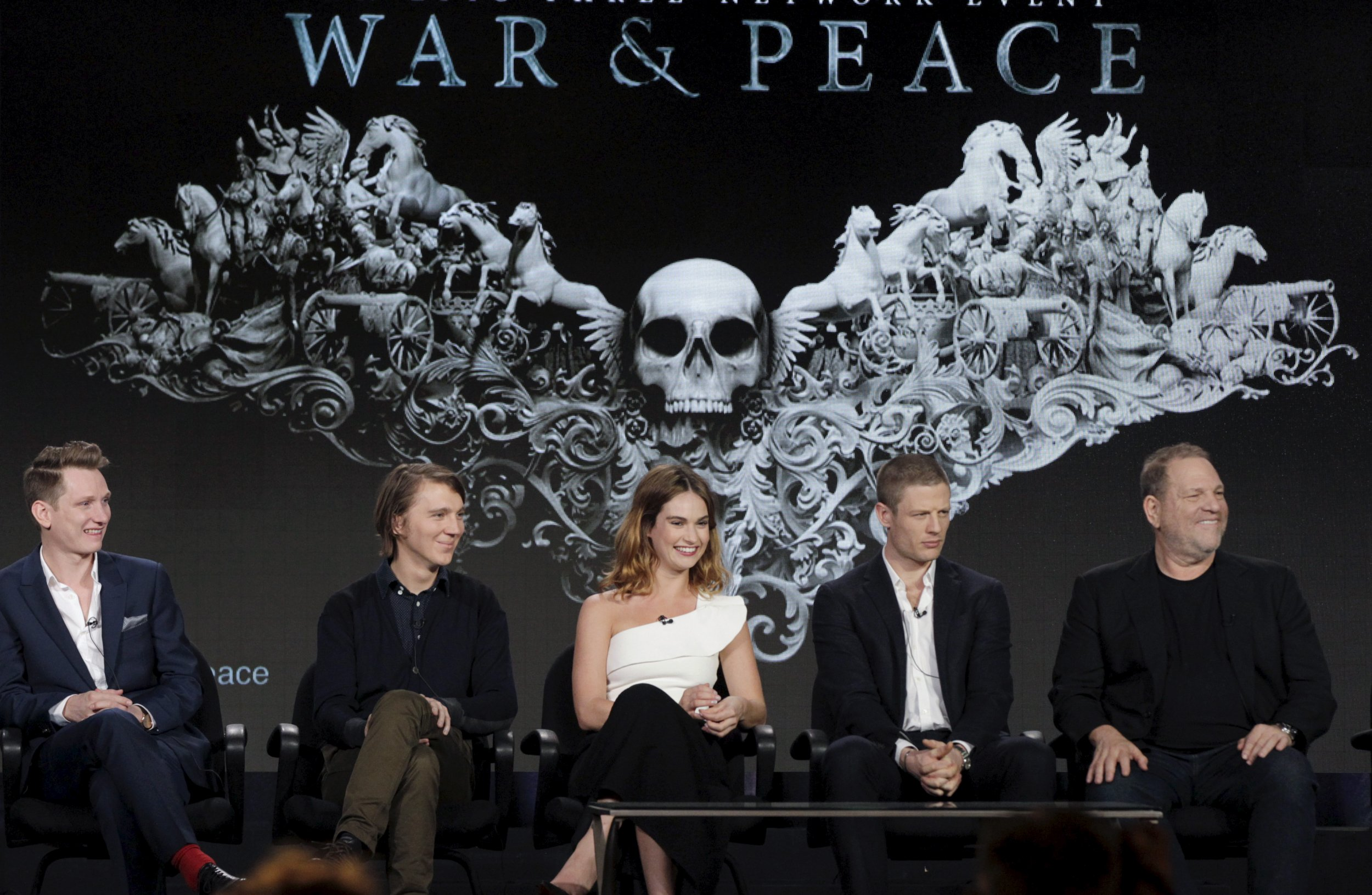 War and Peace cast sit in front of show title card