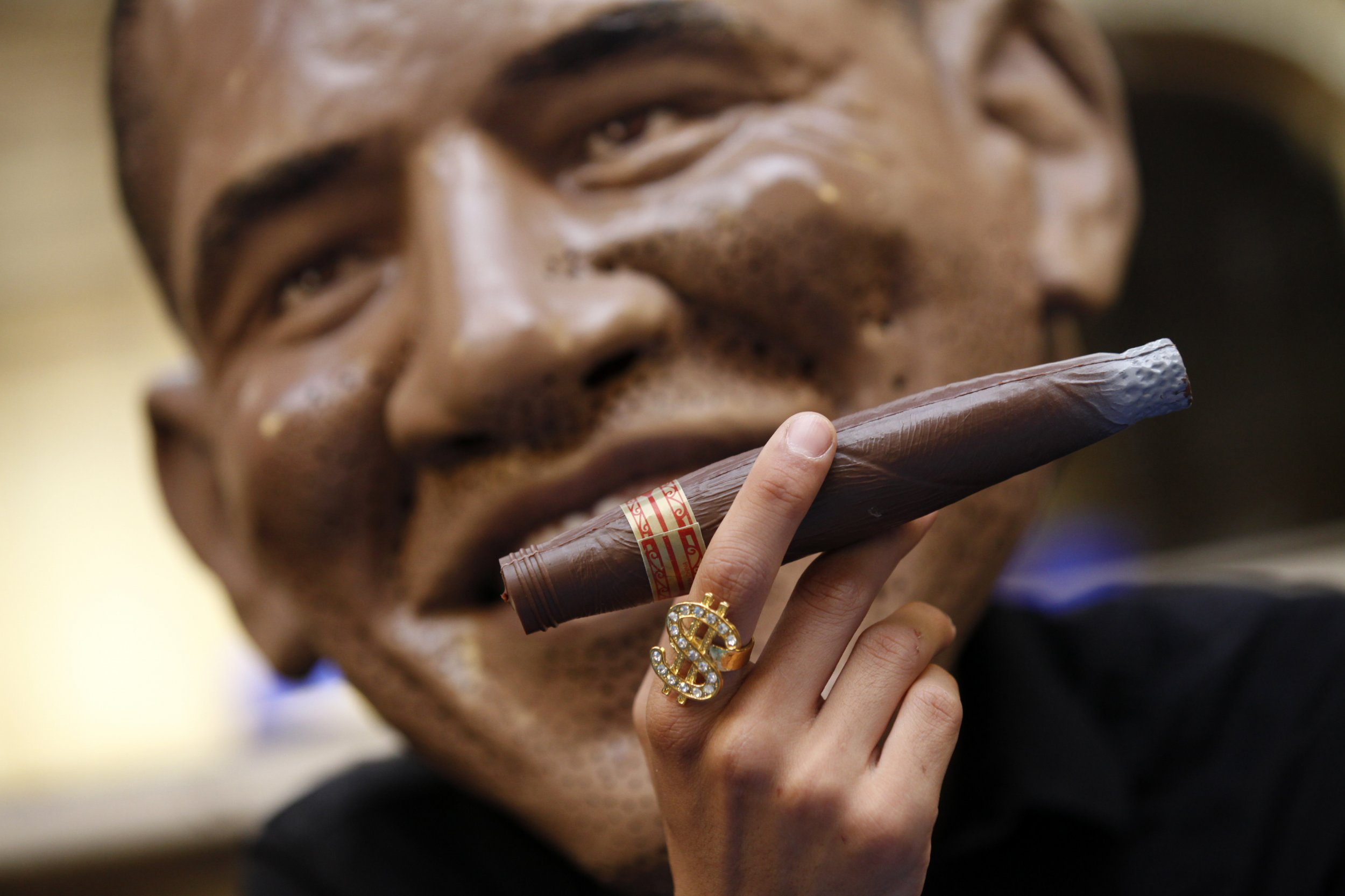 A man with a giant Obama mask smokes a cigar