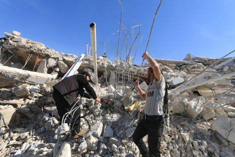 Two men remove rubble at Idlib hospital ruin