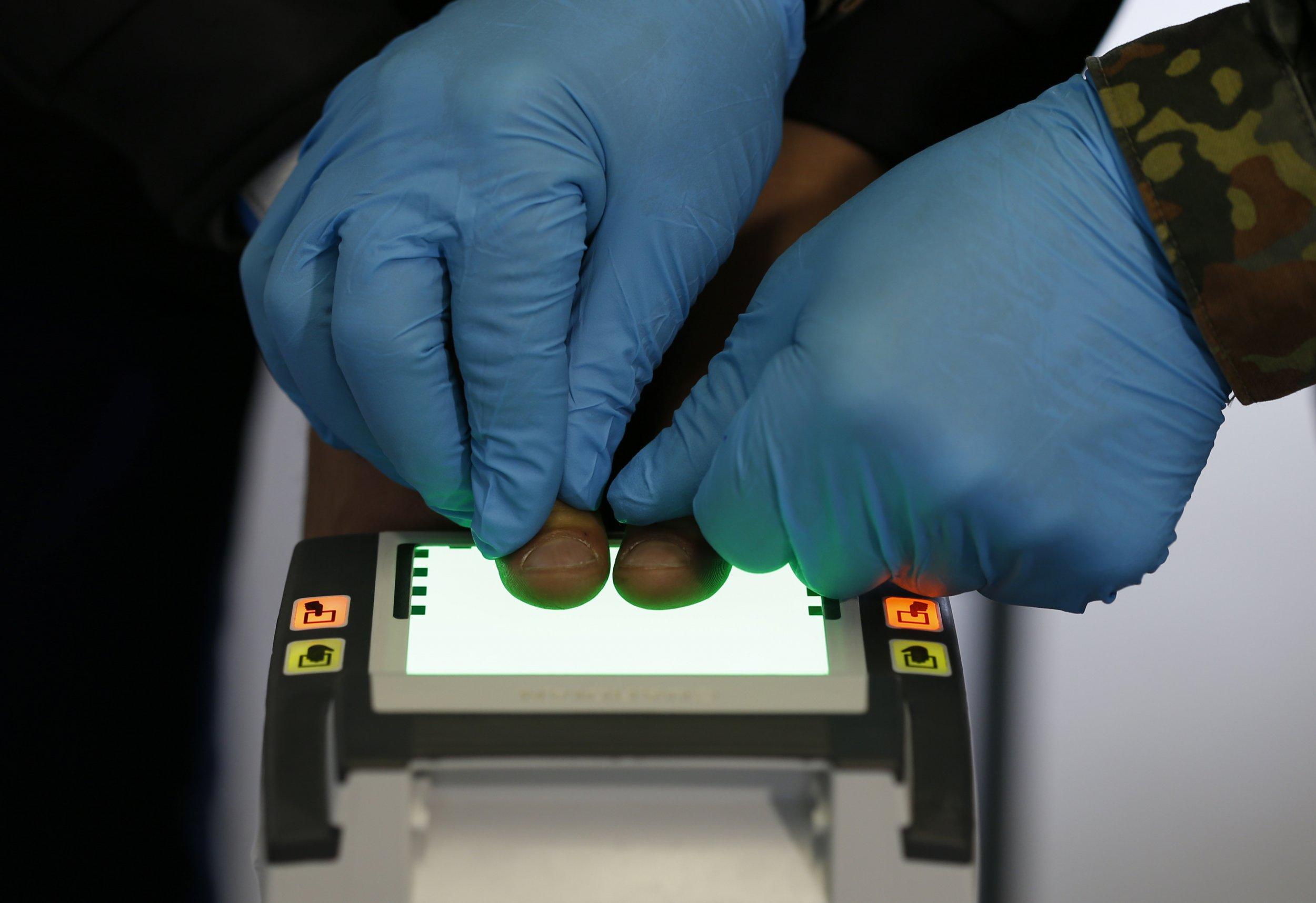 An official scans migrant fingerprints