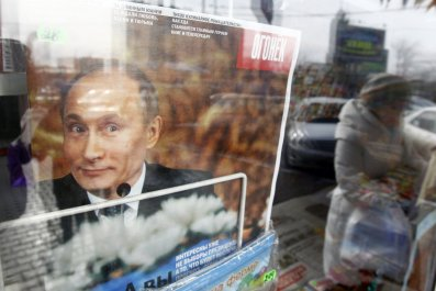 Putin smiles on the cover of a magazine at a kiosk