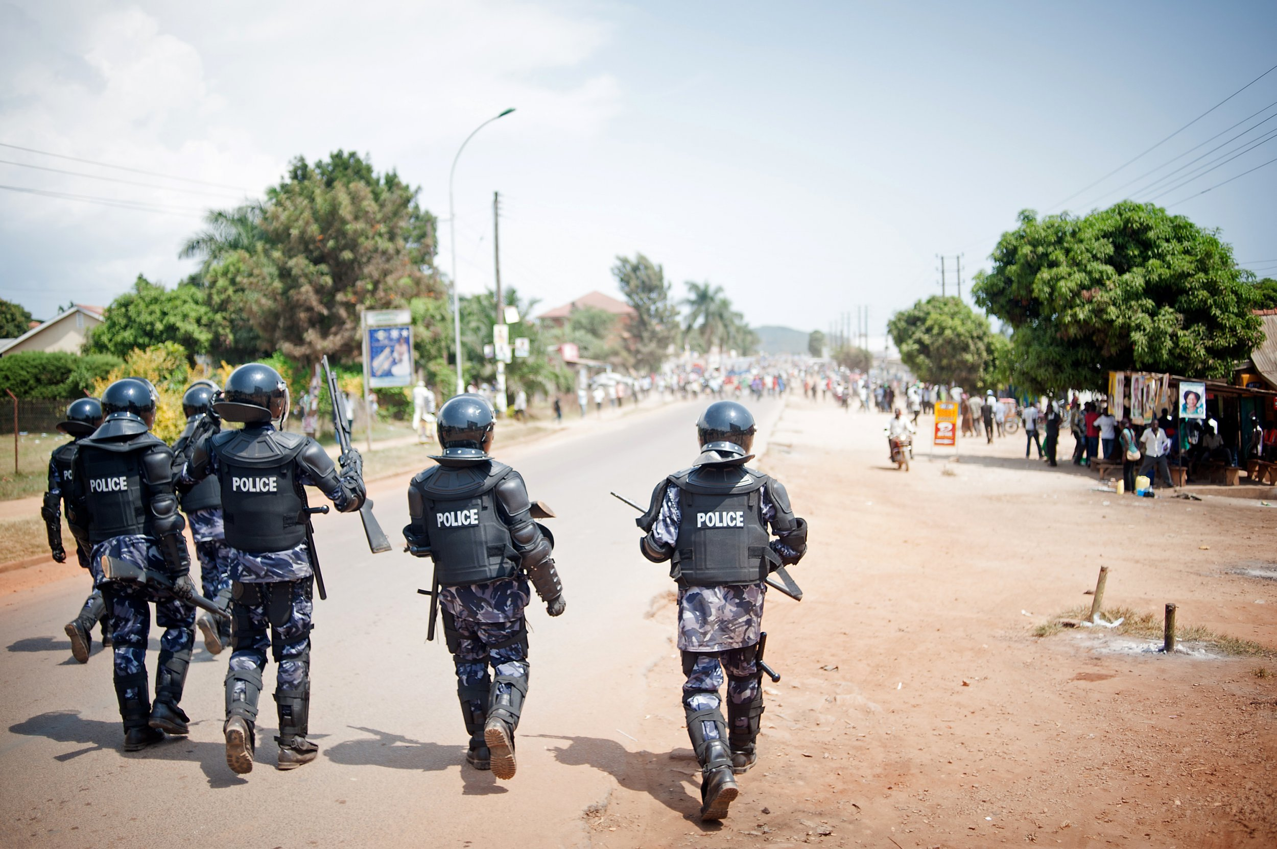 Ugandan riot police advance towards opposition supporters in Ggaba, Kampala.