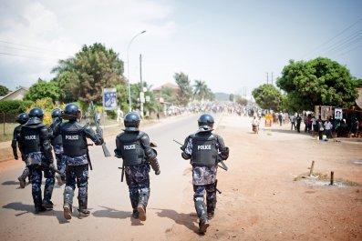 Ugandan riot police advance towards opposition supporters in Ggaba, Kampala.
