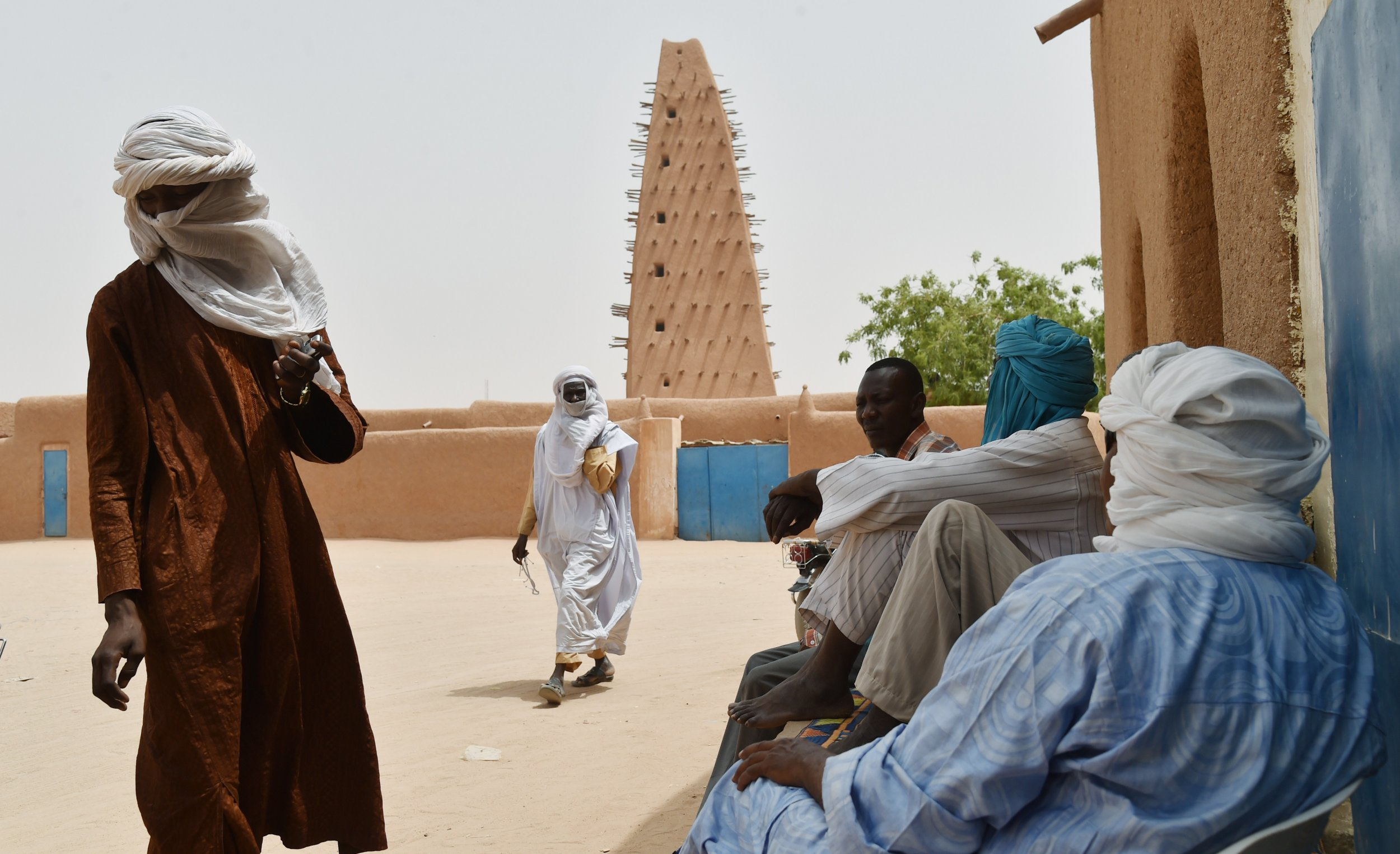 Nigeriens stand near a mosque in Agadez.