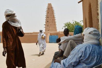 Nigeriens stand near a mosque in Agadez.