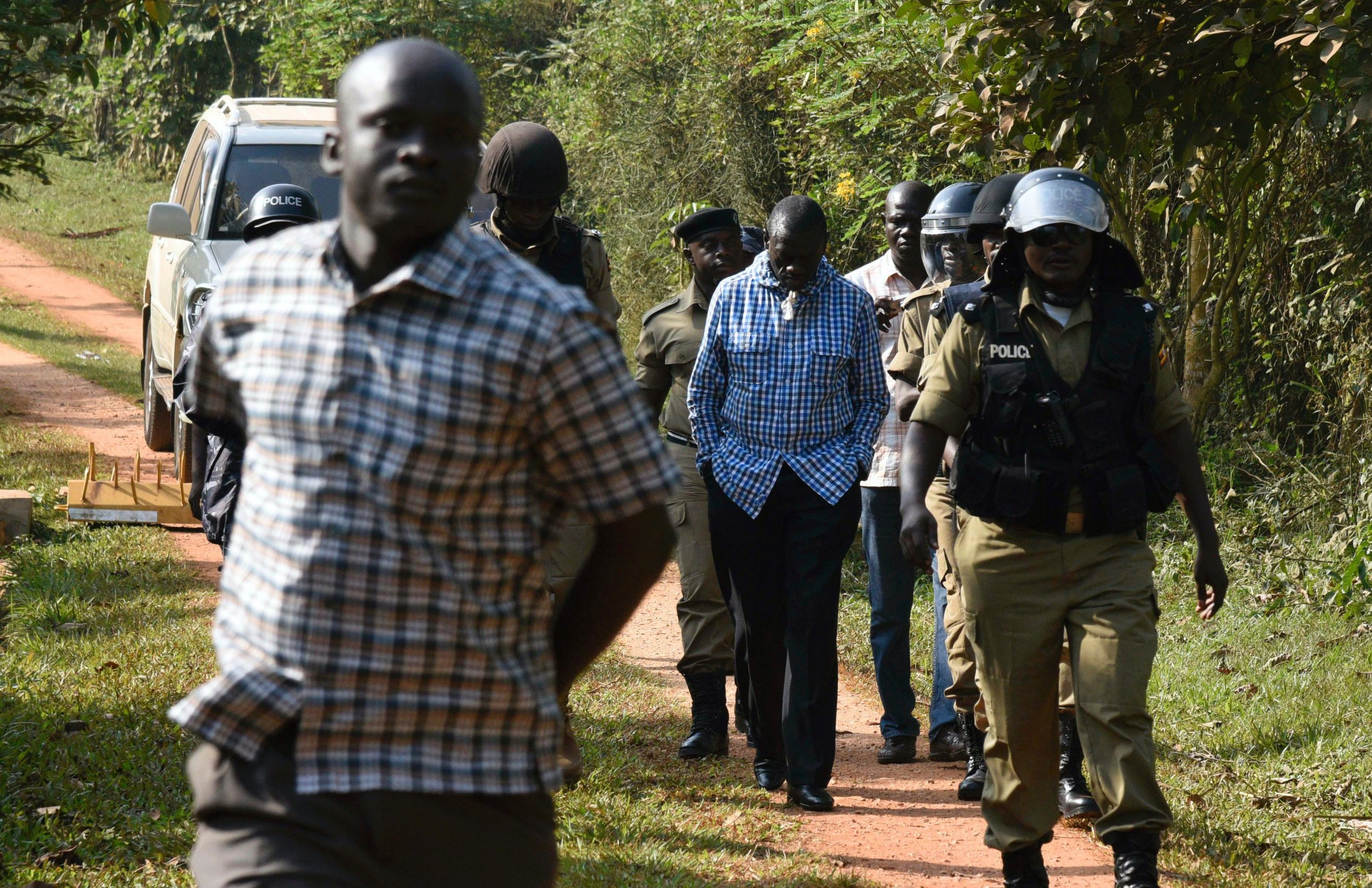 Kizza Besigye is escorted to a police vehicle in Kampala.