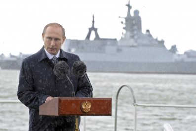 Putin speaks in front of a Russian warship