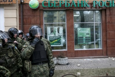 Ukrainian riot police stand in front of vandalised Russian bank
