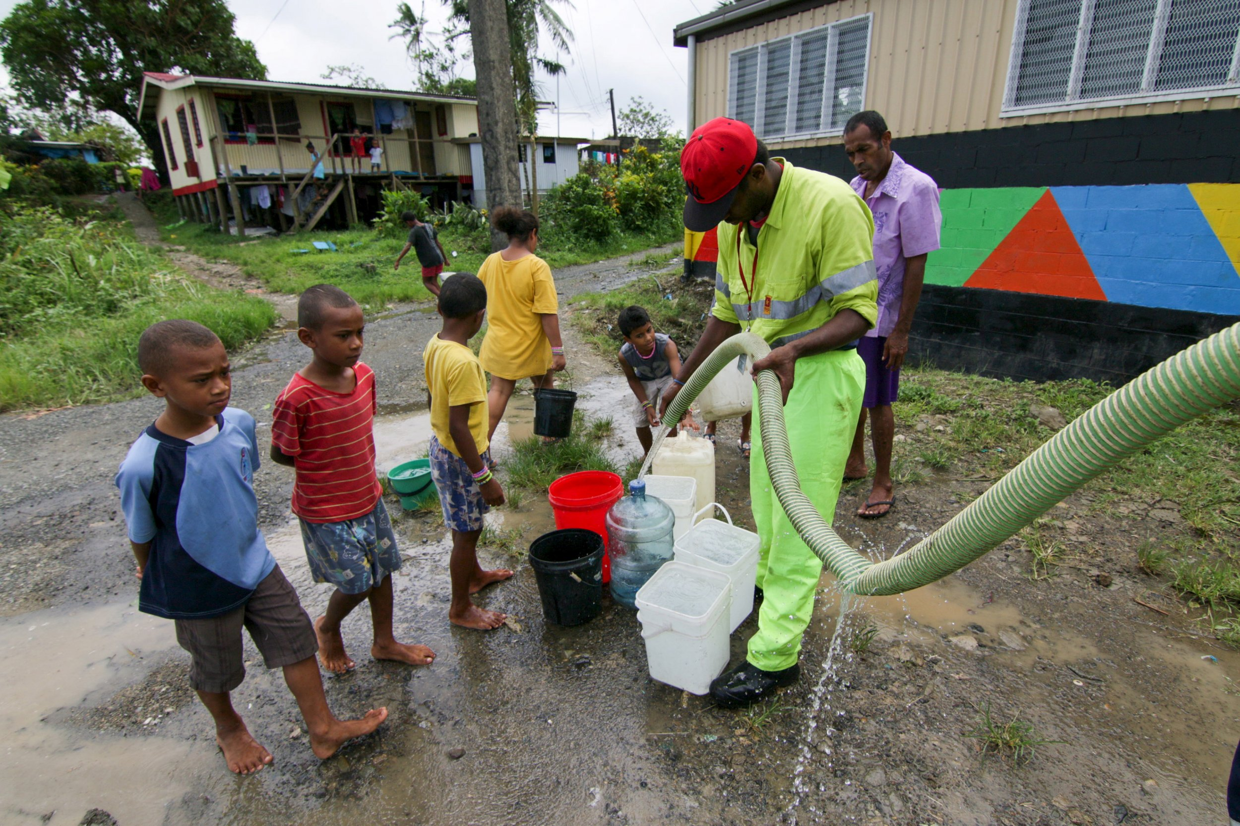 Worker-fills-buckets-fresh-water-cyclone-Fiji.