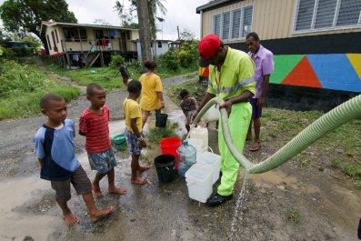 Worker-fills-buckets-fresh-water-cyclone-Fiji.