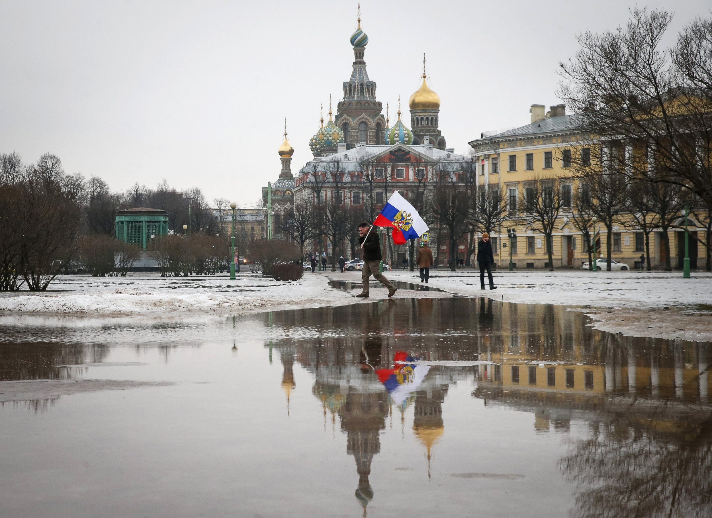 Man walks with a Russian flag in front of an ornate church