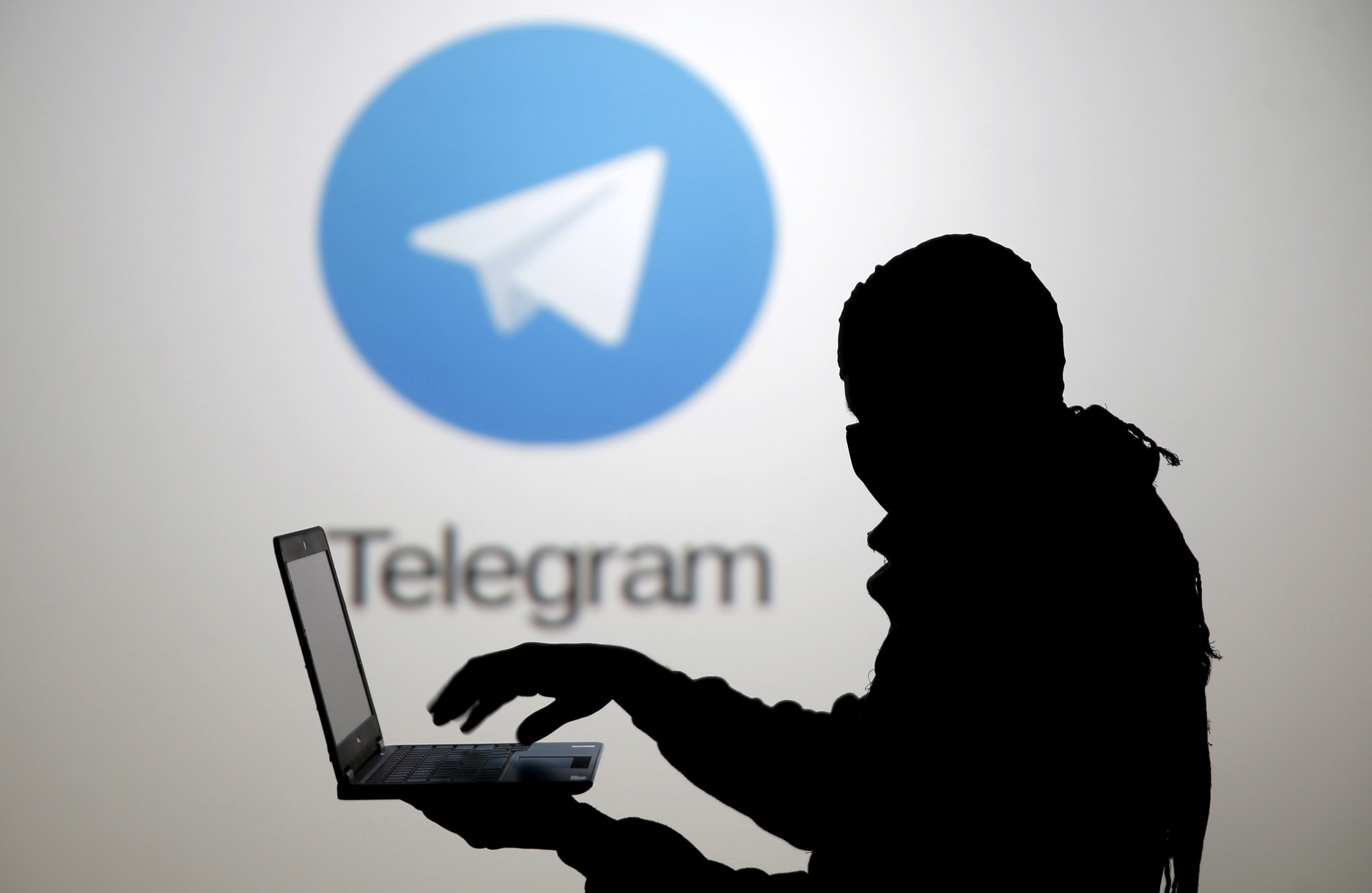 Silhouette of a man with a lap top in front of the Telegram logo