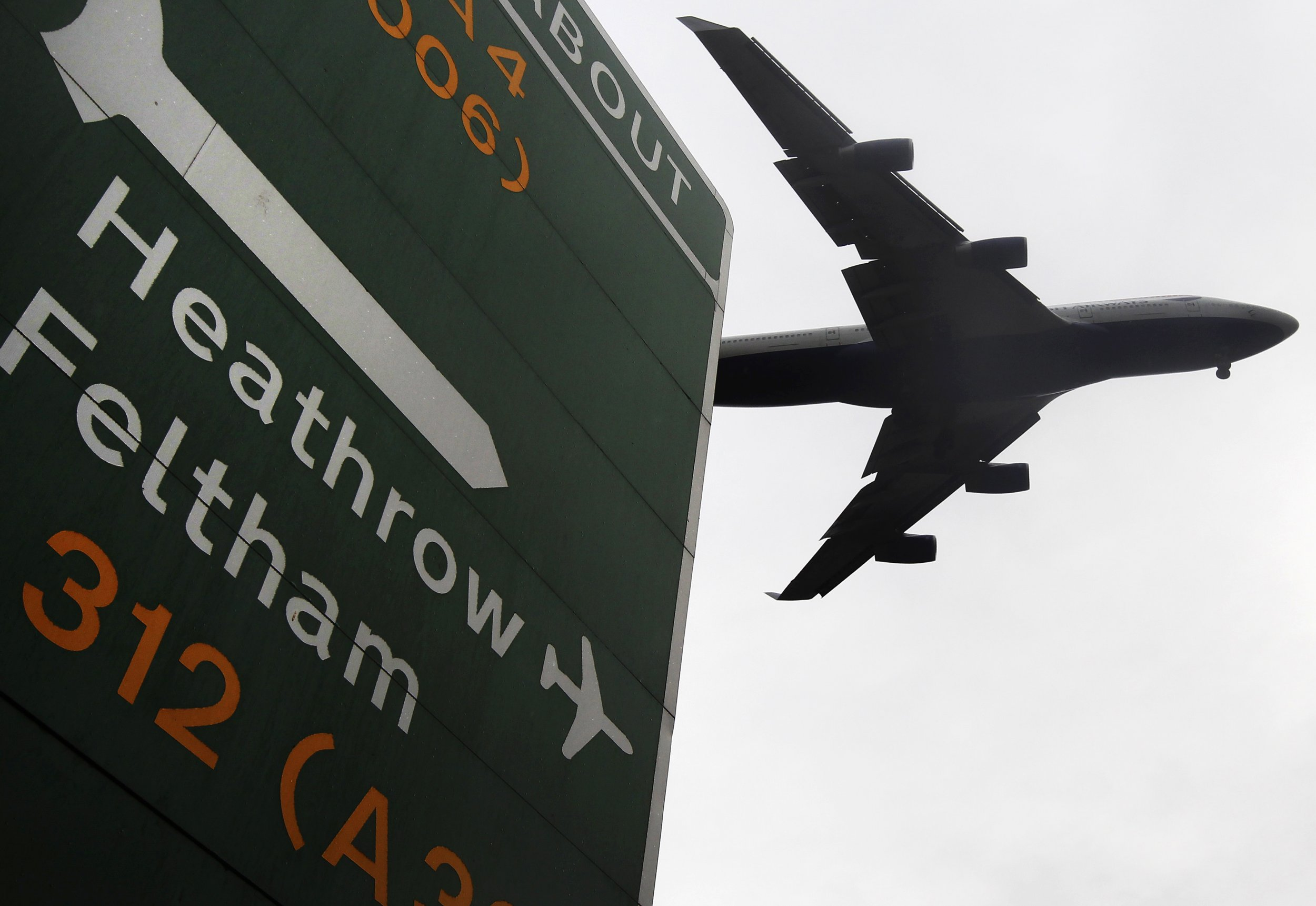 Plane flies above a sign to Heathrow airport