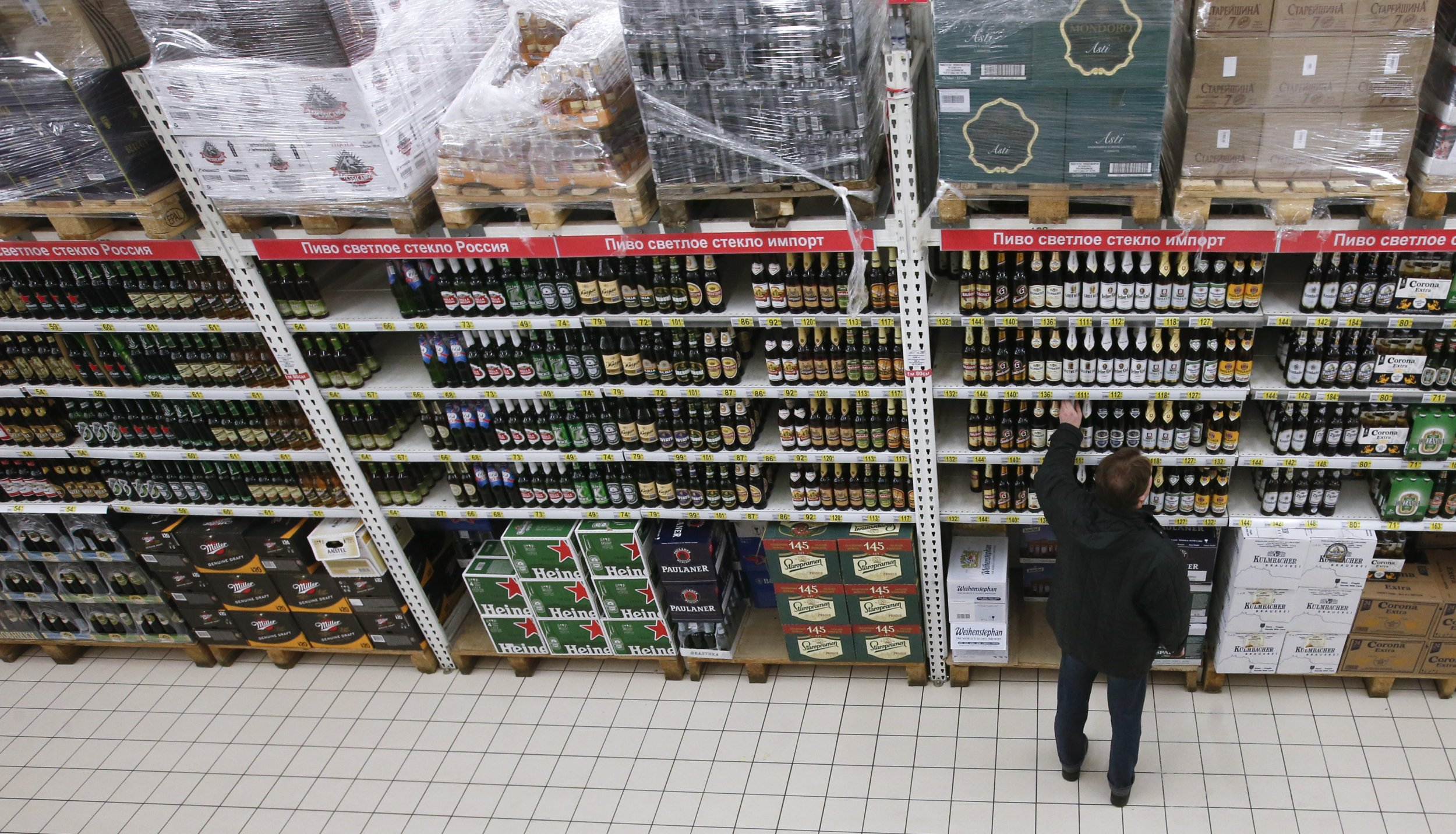 Russian shopper reaches towards a supermarket aisle of alcohol