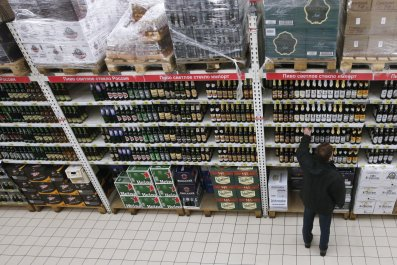 Russian shopper reaches towards a supermarket aisle of alcohol