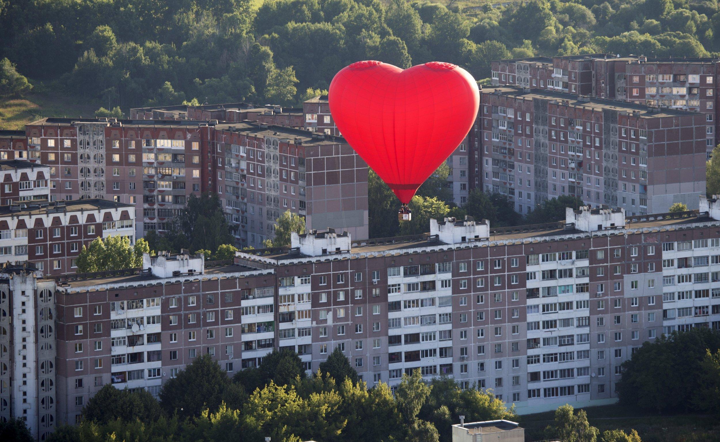 Heartshaped hot air balloon flies above communist buildings