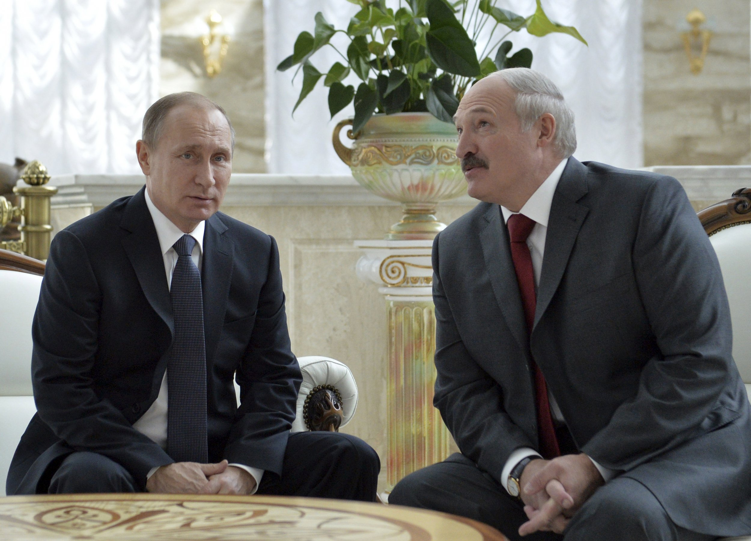 Putin sits next to Lukashenko