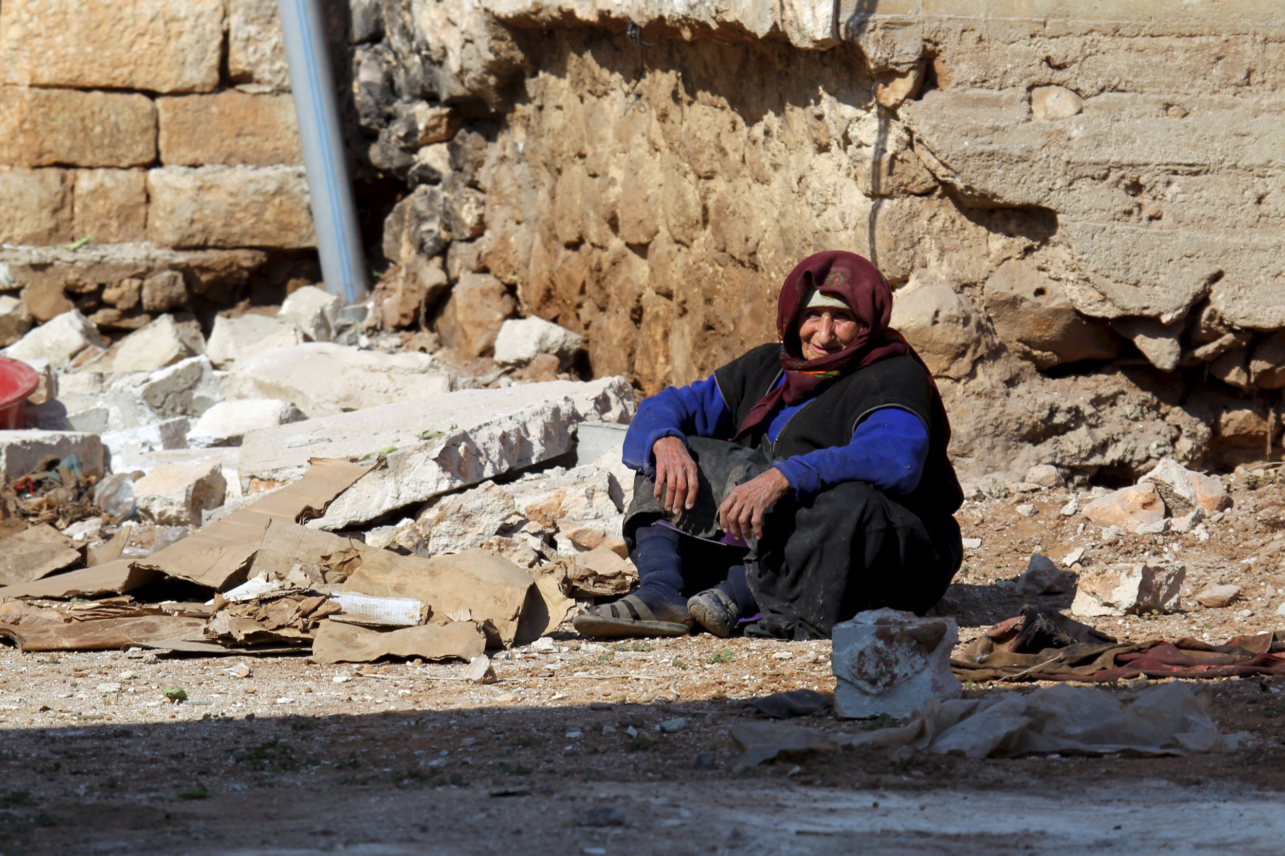 A woman rests on the ground in Aleppo.