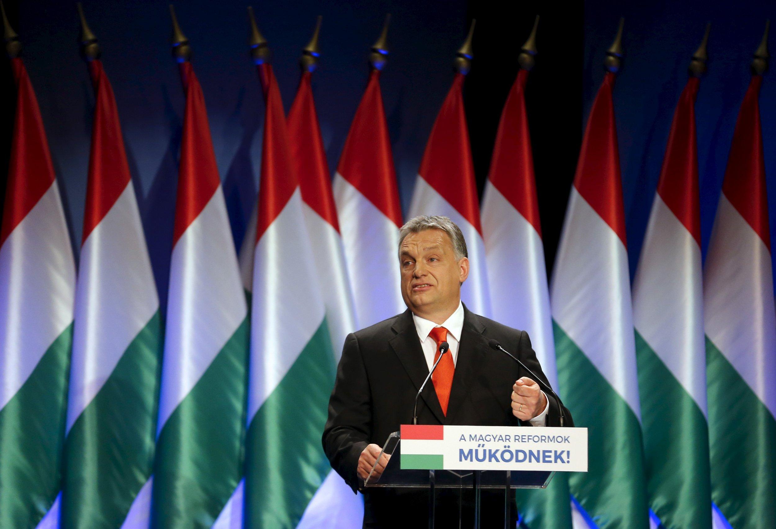 Viktor Orban speaks in front of Hungarian flags