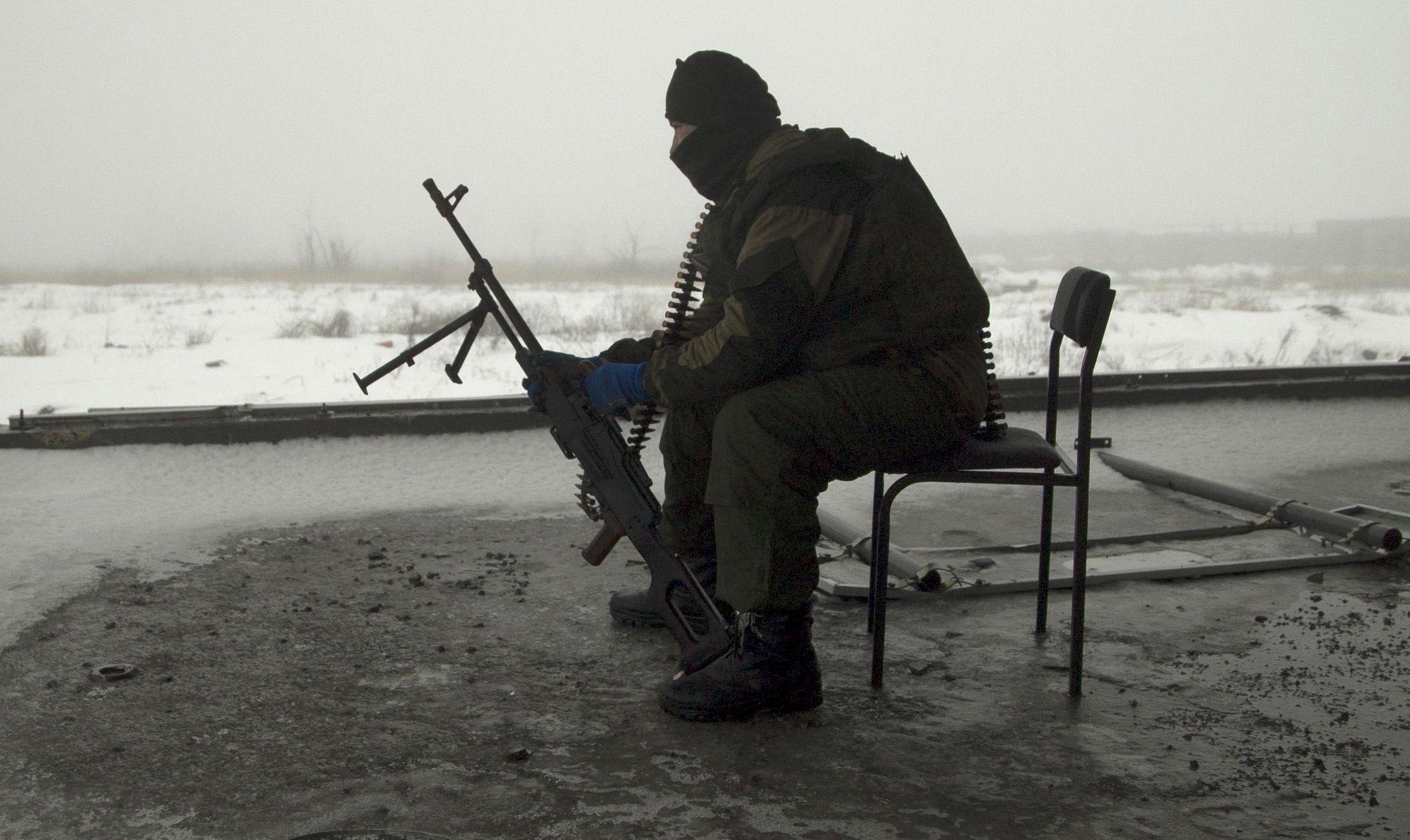 Ukraine rebel sits with his gun in Donetsk