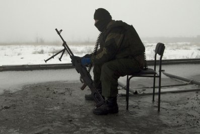 Ukraine rebel sits with his gun in Donetsk