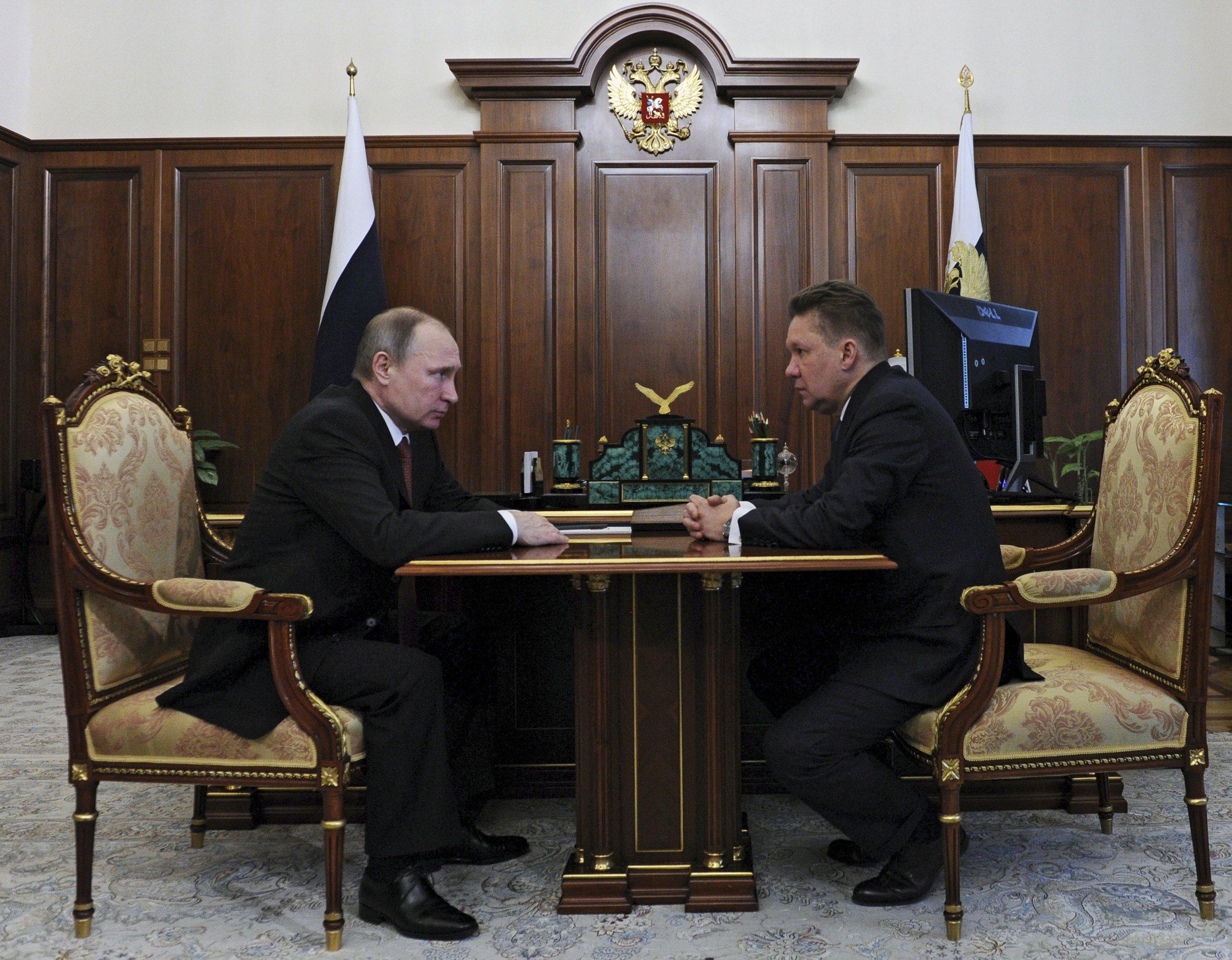 Putin looks opposite Miller at his desk