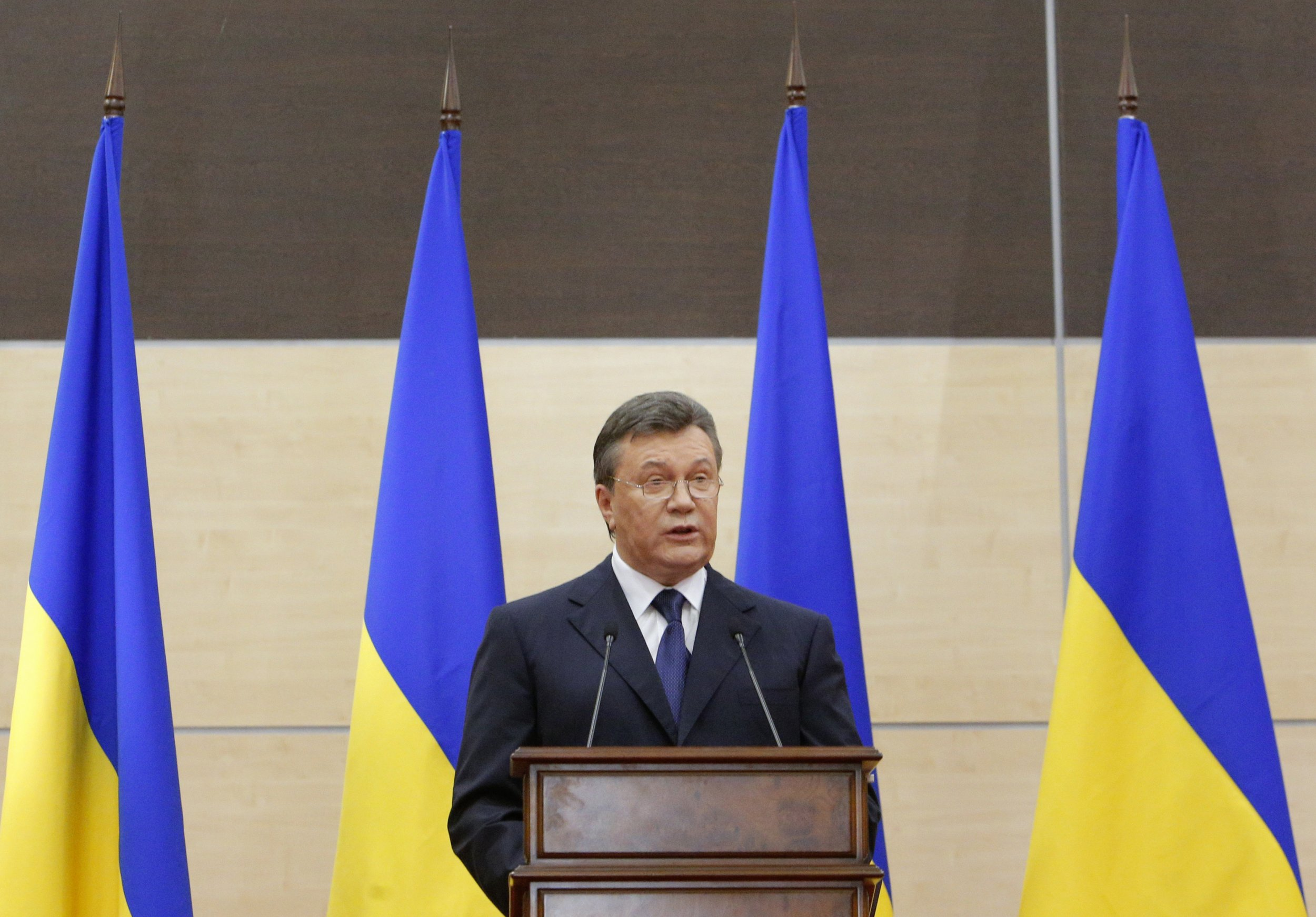 Yanukovych speaks in front of Ukrainian flags