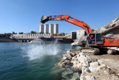 Building crew digs into the Tigris river above the dam