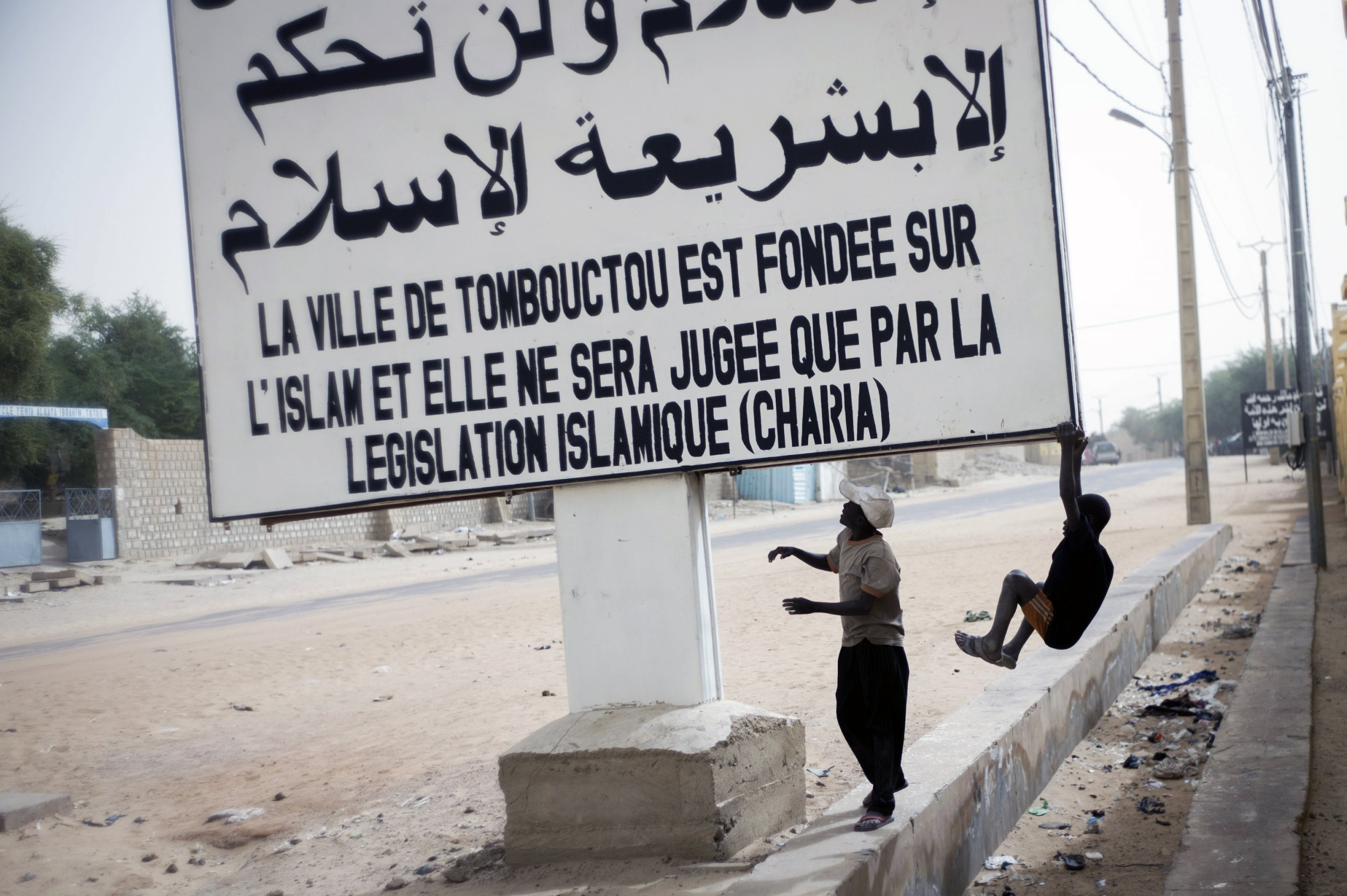 Children play on a sign in Timbuktu, northern Mali.