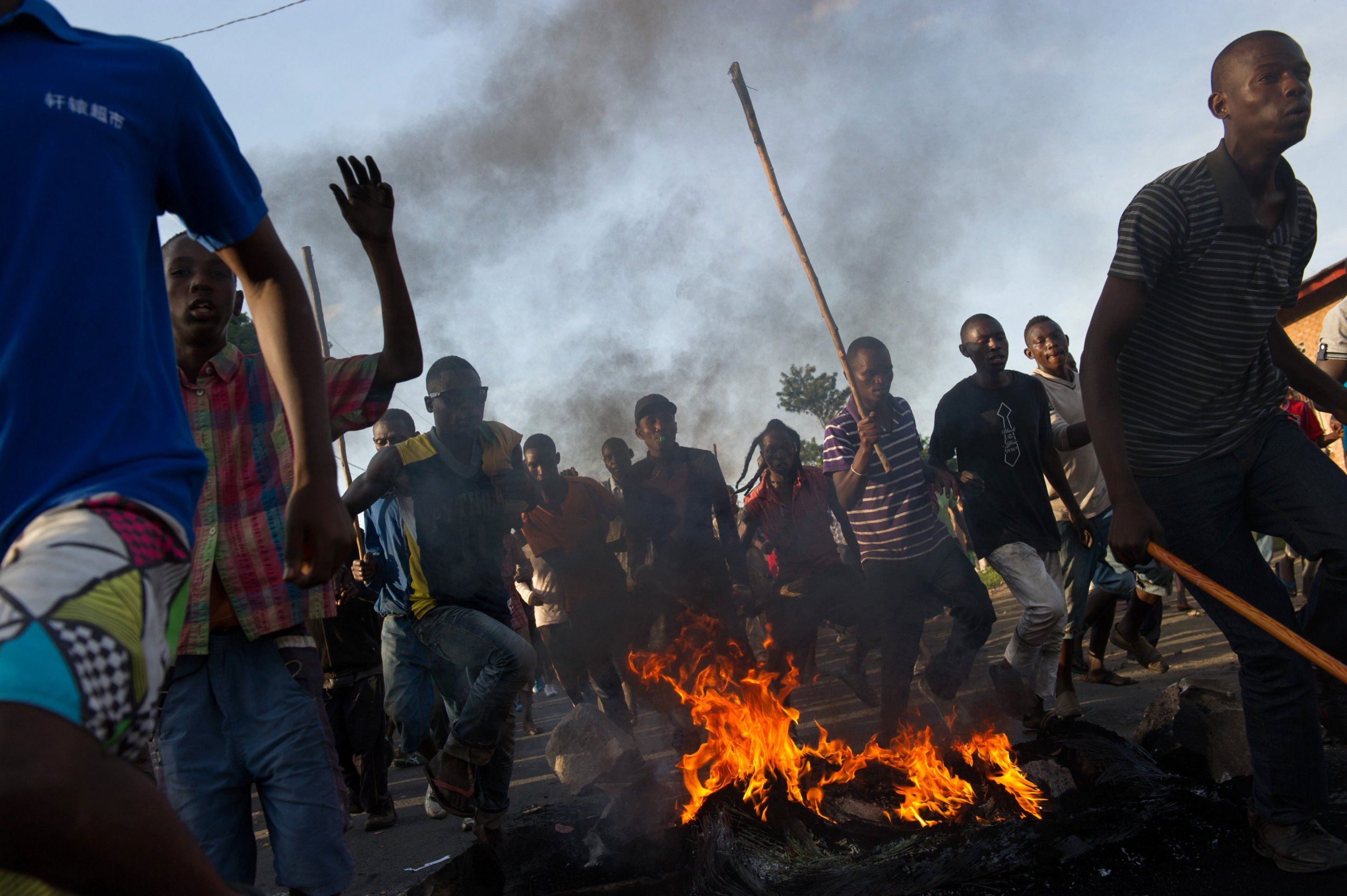 Protesters in Burundi run towards police lines.
