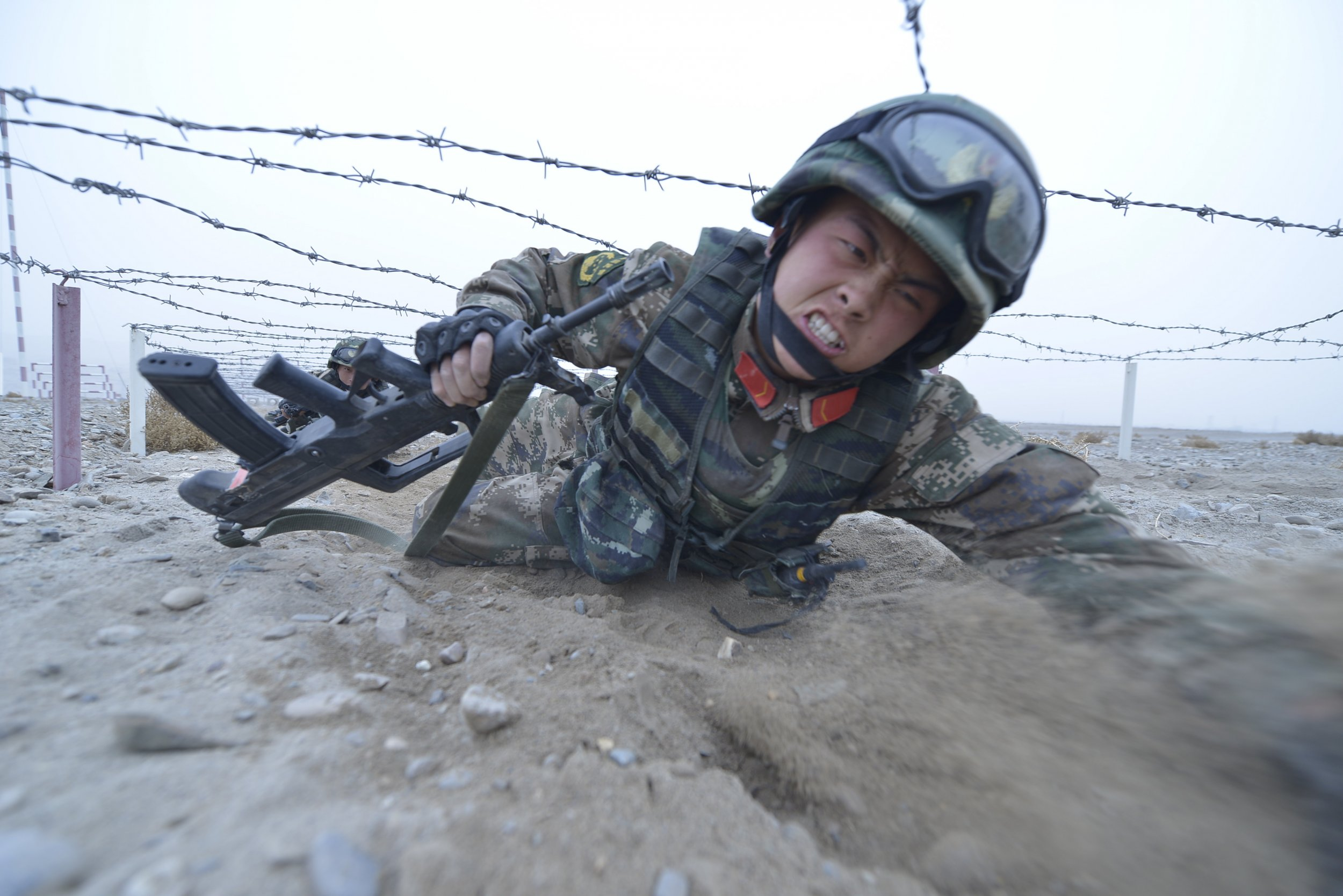 Chinese soldier crawls under barbed wire