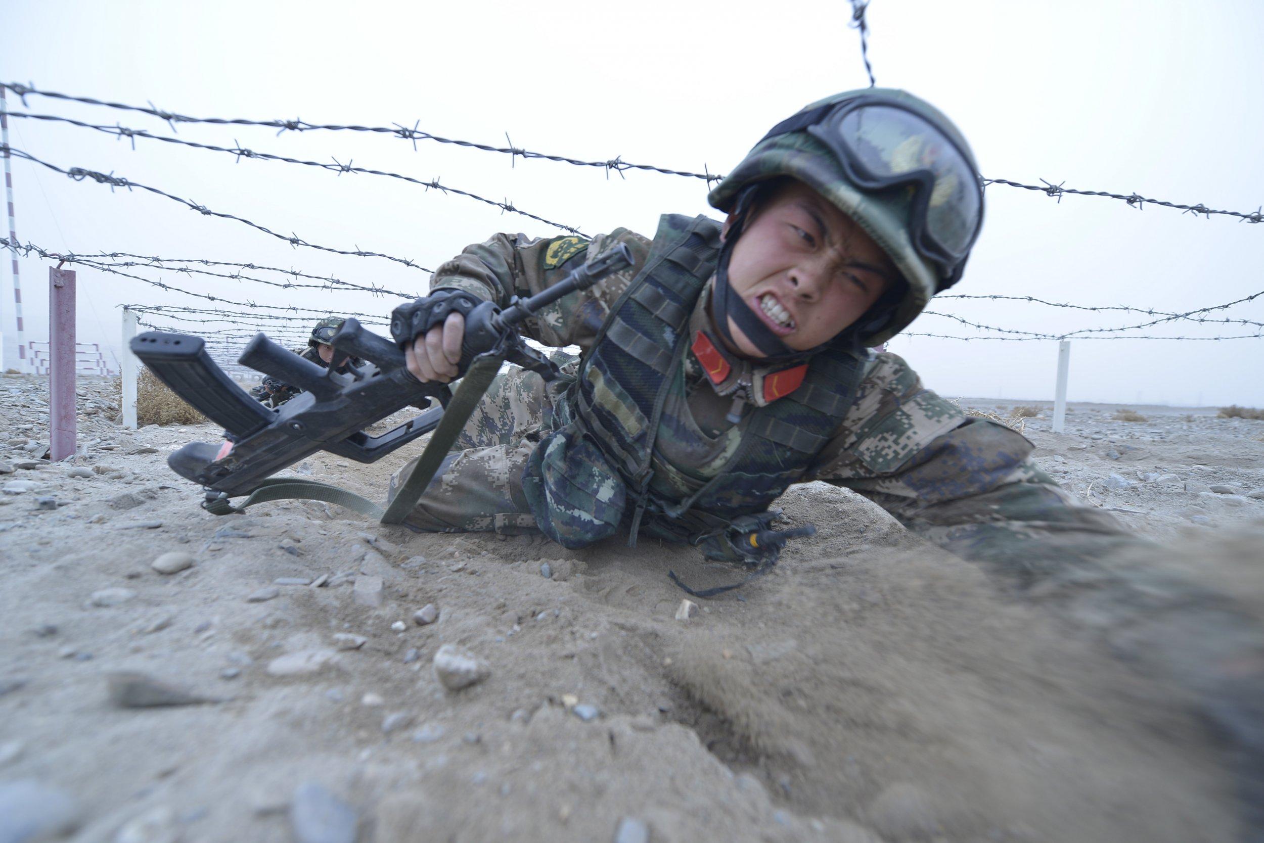 Chinese soldier crawls under barbed wire