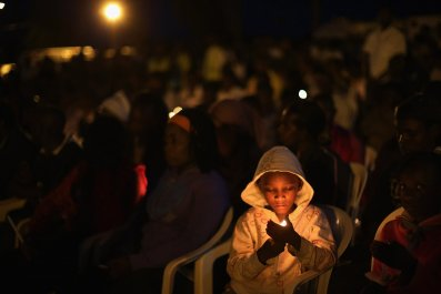 A child holds a candle at a Rwandan genocide memorial.