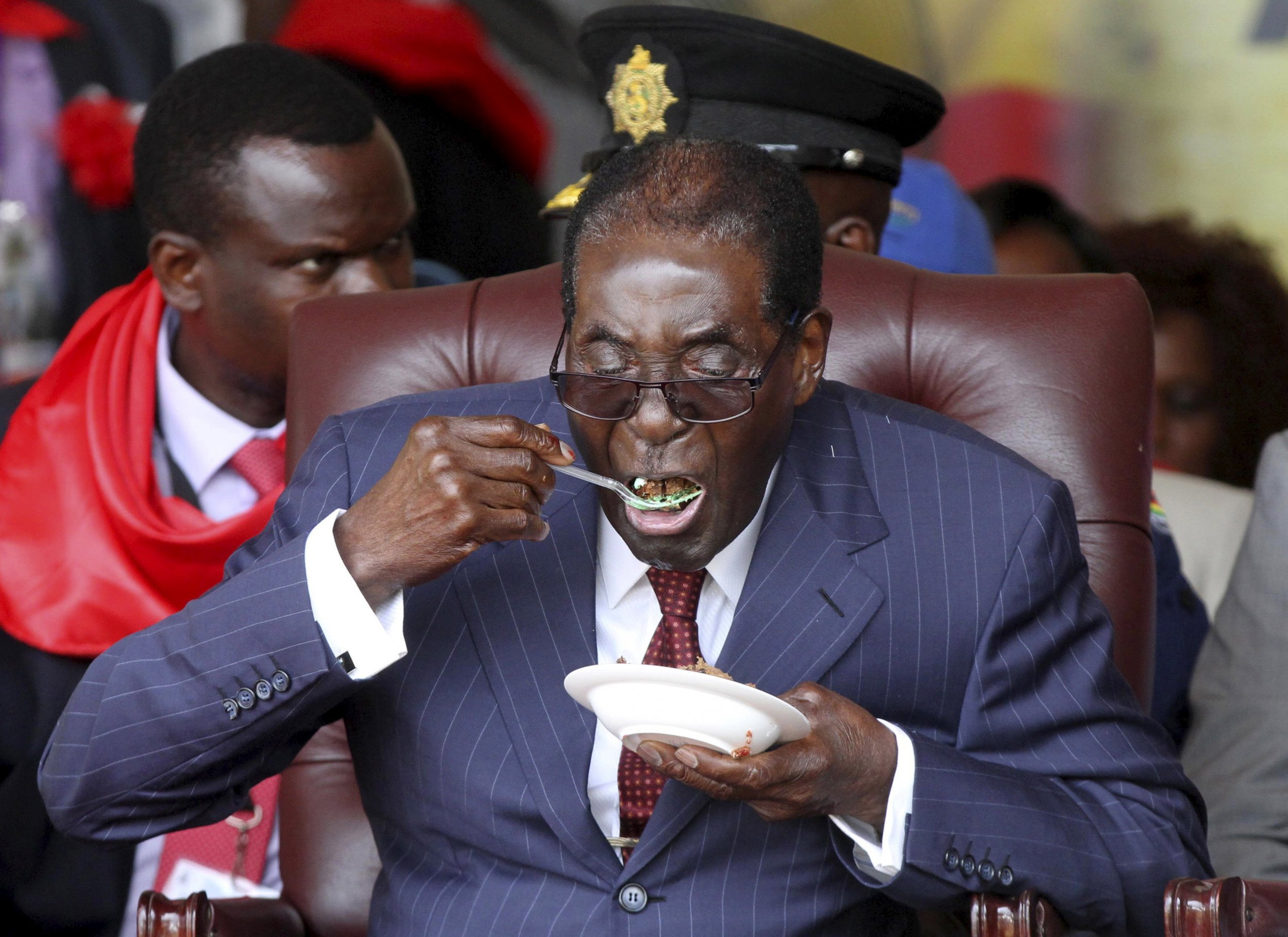 Zimbabwe President Robert Mugabe eats cake at his 92nd birthday celebrations.