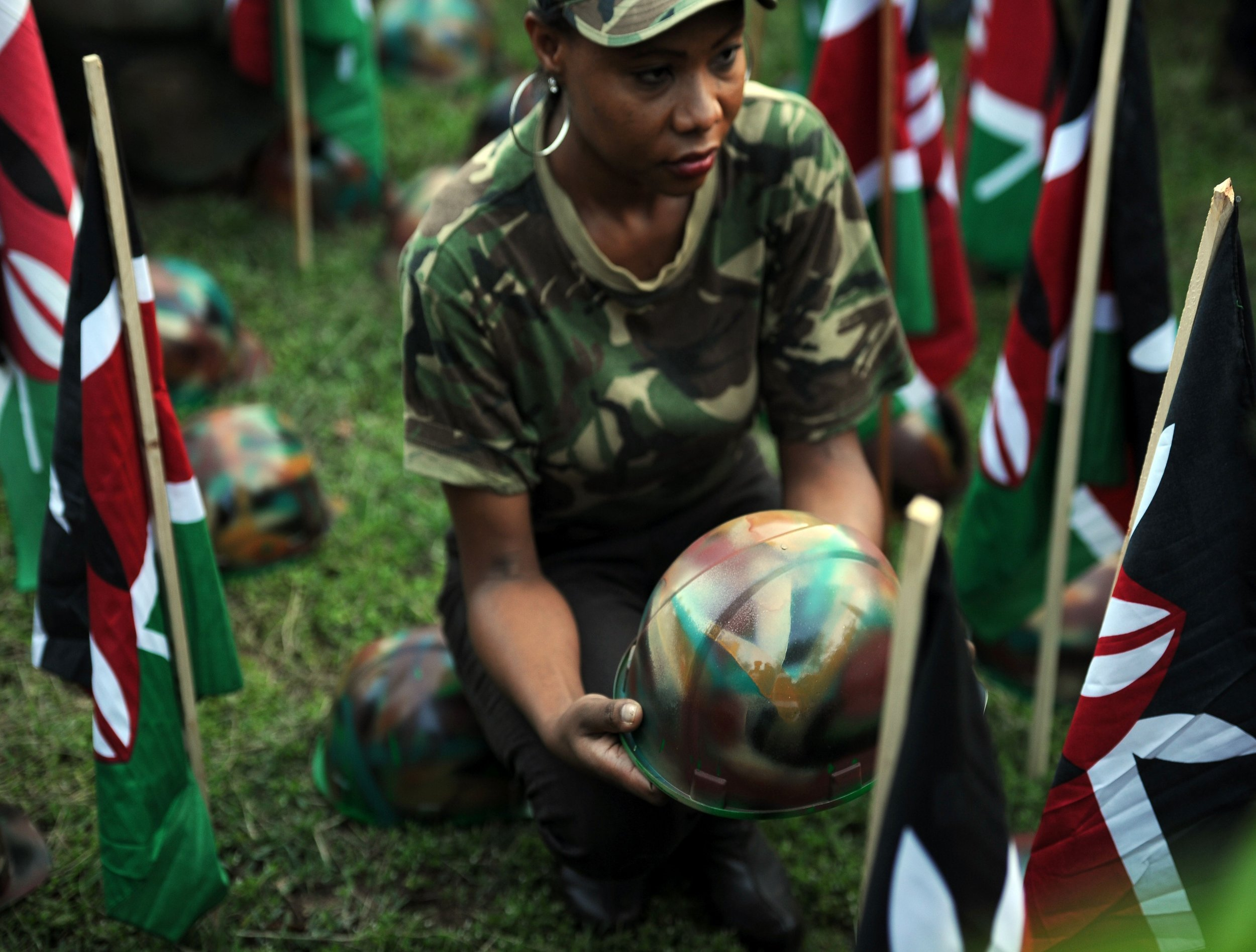 A woman holds a helmet at a vigil for Kenyan soldiers killed by Al-Shabab.