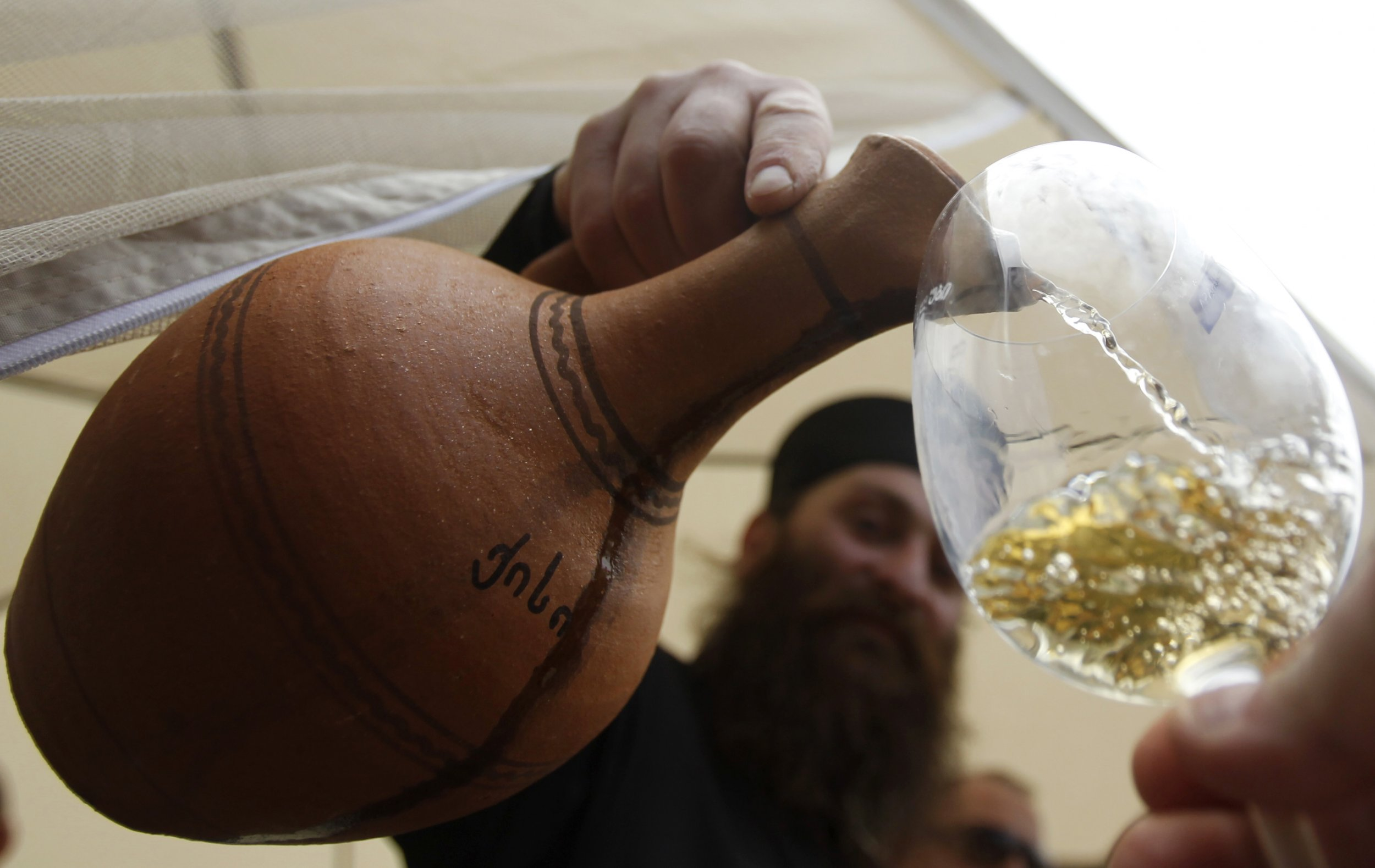 Priest pours Georgian wine in glass
