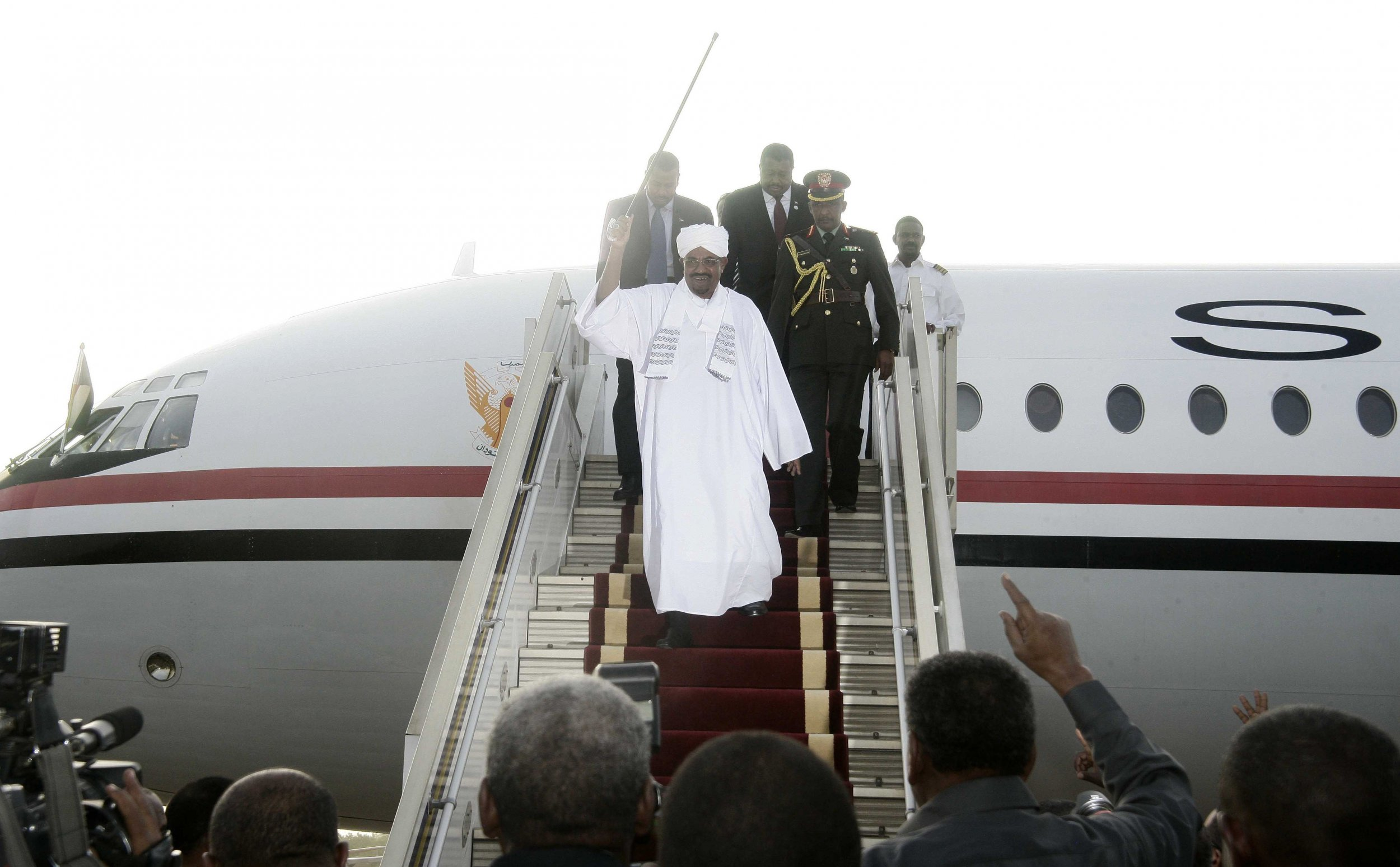 Sudanese President Omar al-Bashir waves upon returning to Khartoum from Johannesburg.