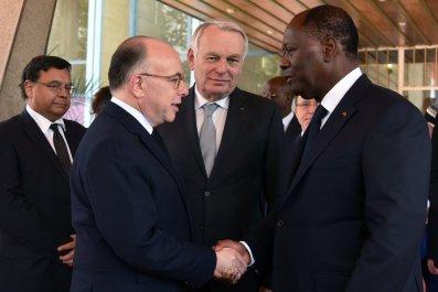 French interior minister Bernard Cazeneuve greets Ivory Coast President Alassane Ouattara.