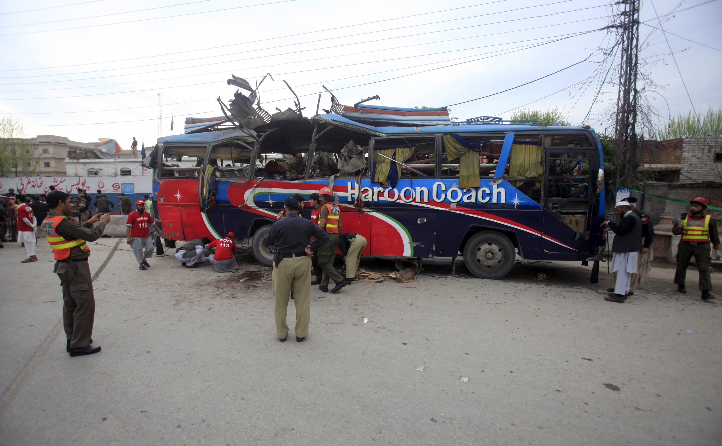Police walk near a bus damaged by a bomb in Peshawar, Pakistan.