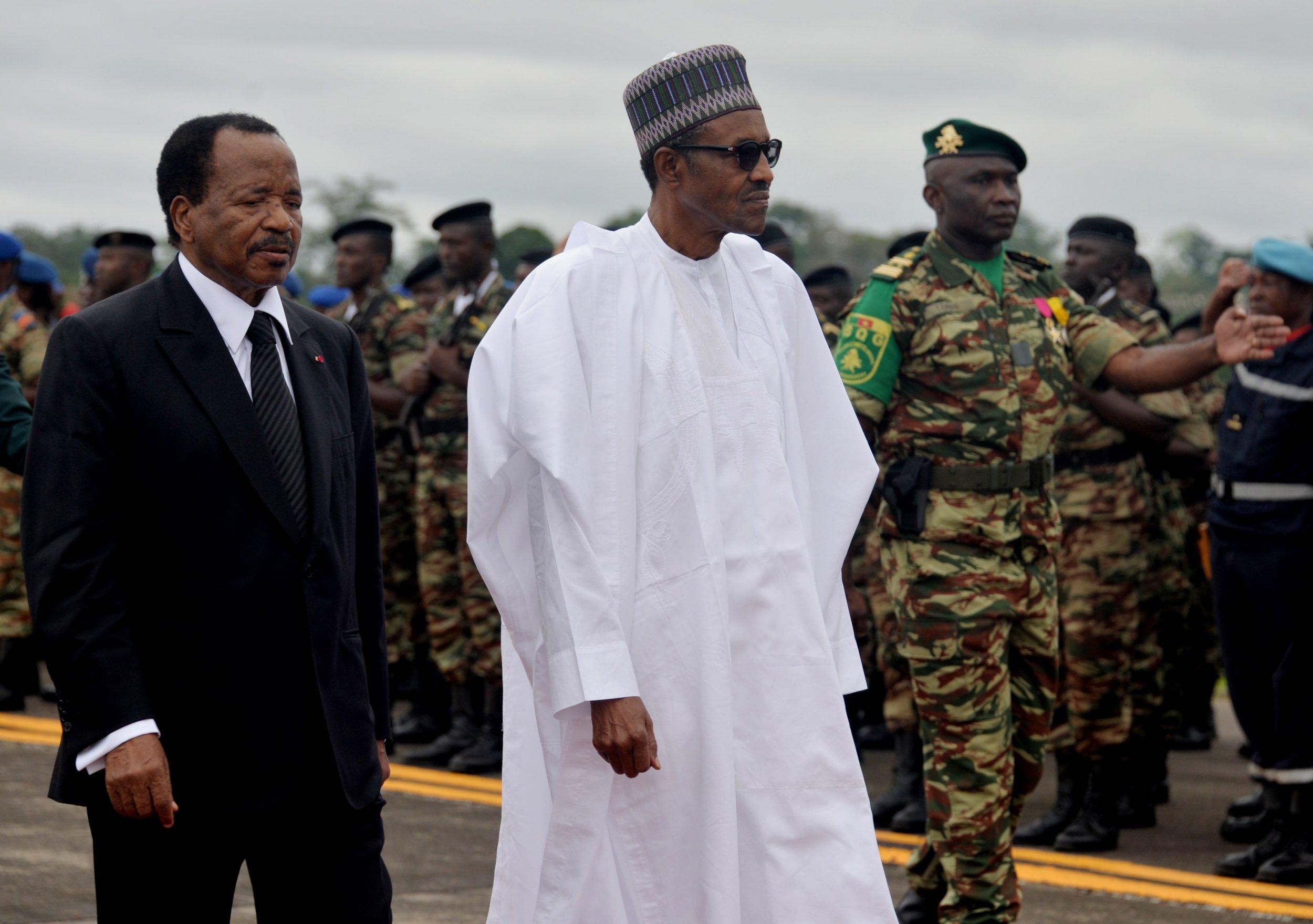 Cameroonian President Paul Biya walks with Nigerian President Muhammadu Buhari.