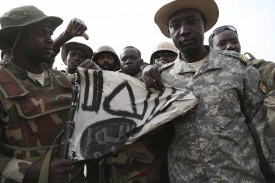 Nigerien soldiers hold up a Boko Haram flag.