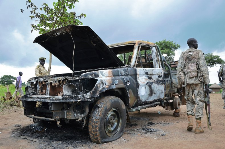 South Sudanese soldiers walk past a burned out car.