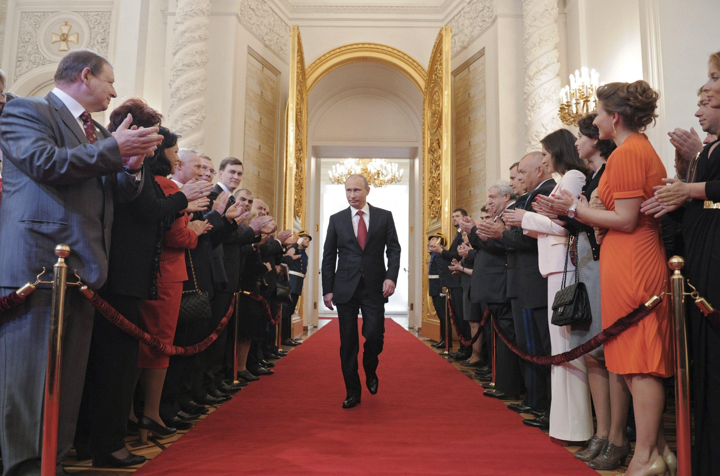 Putin walks to applause in the Kremlin