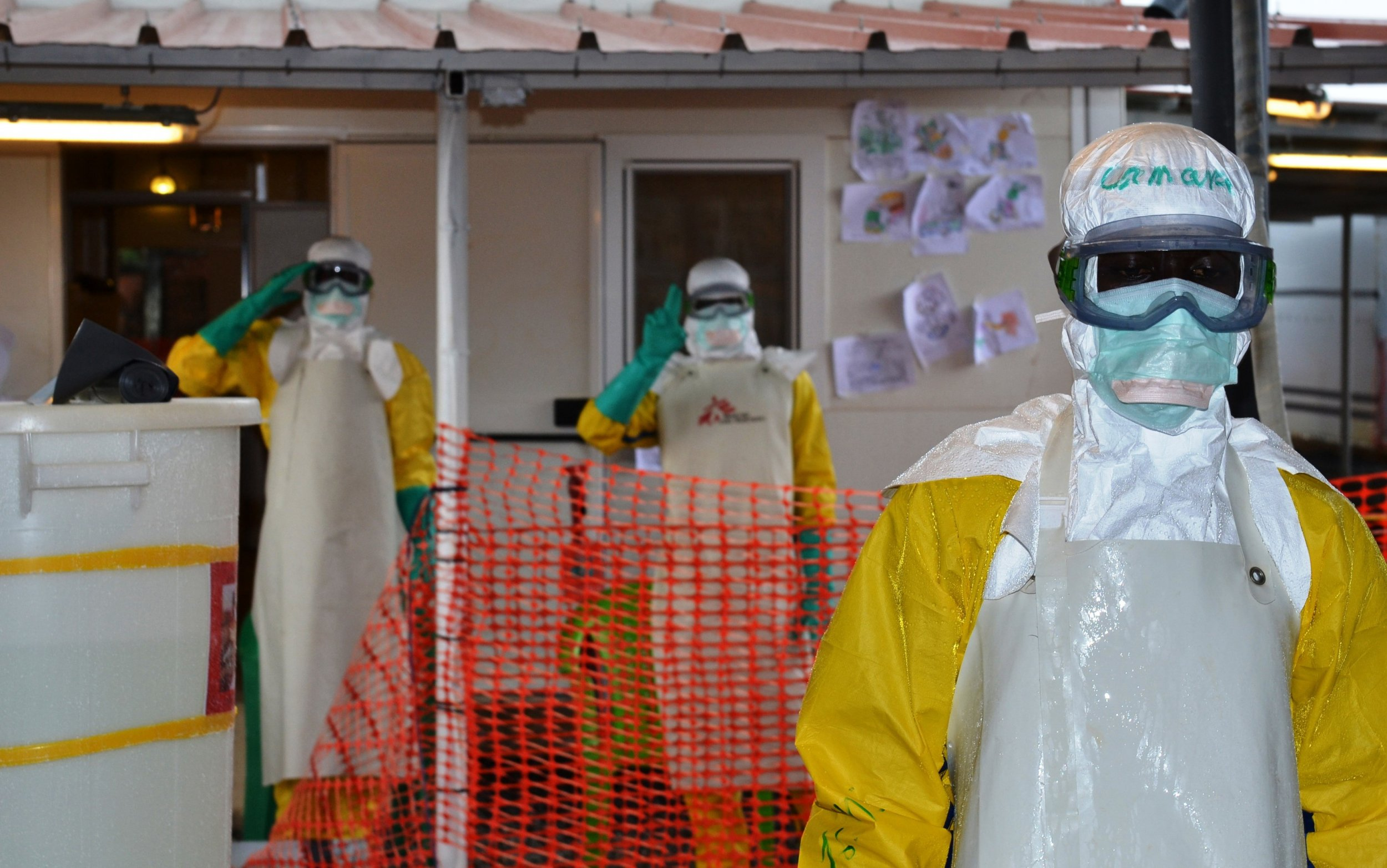 Ebola health workers gesture in Guinea.