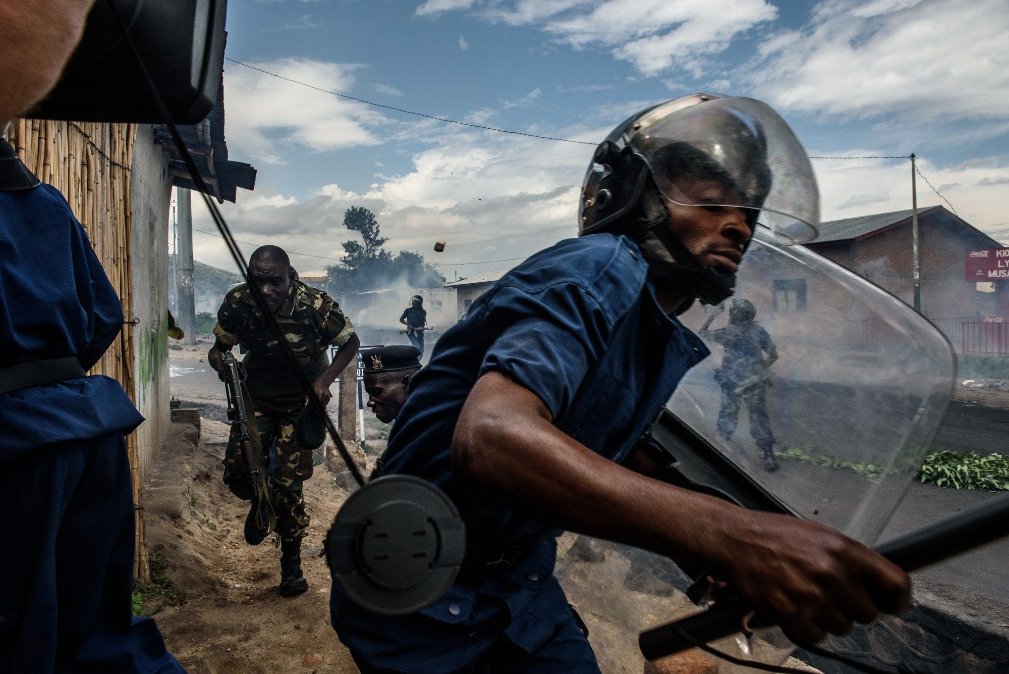 A Burundian police officer runs after protestors in Bujumbura.