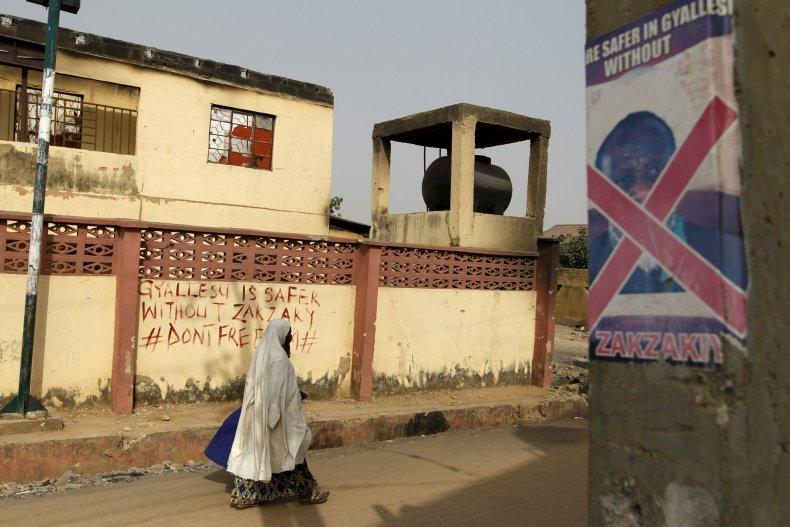 A woman walks past anti-Zakzaky graffiti in Zaria.