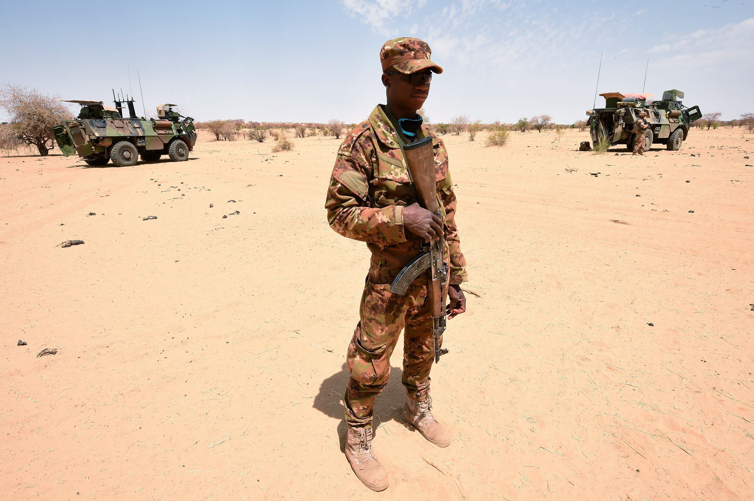 A Malian soldier patrols with French soldiers.
